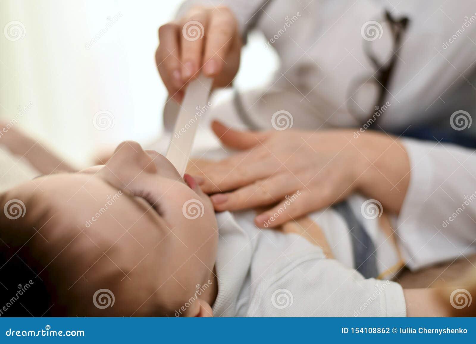 Der Doktor überprüft die Kehle eines Kindes