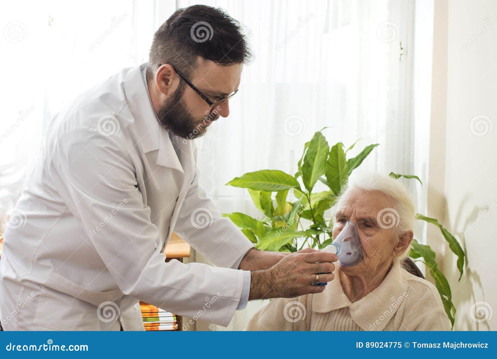 Der Doktor hält Inhalator das Gesicht einer alten Frau