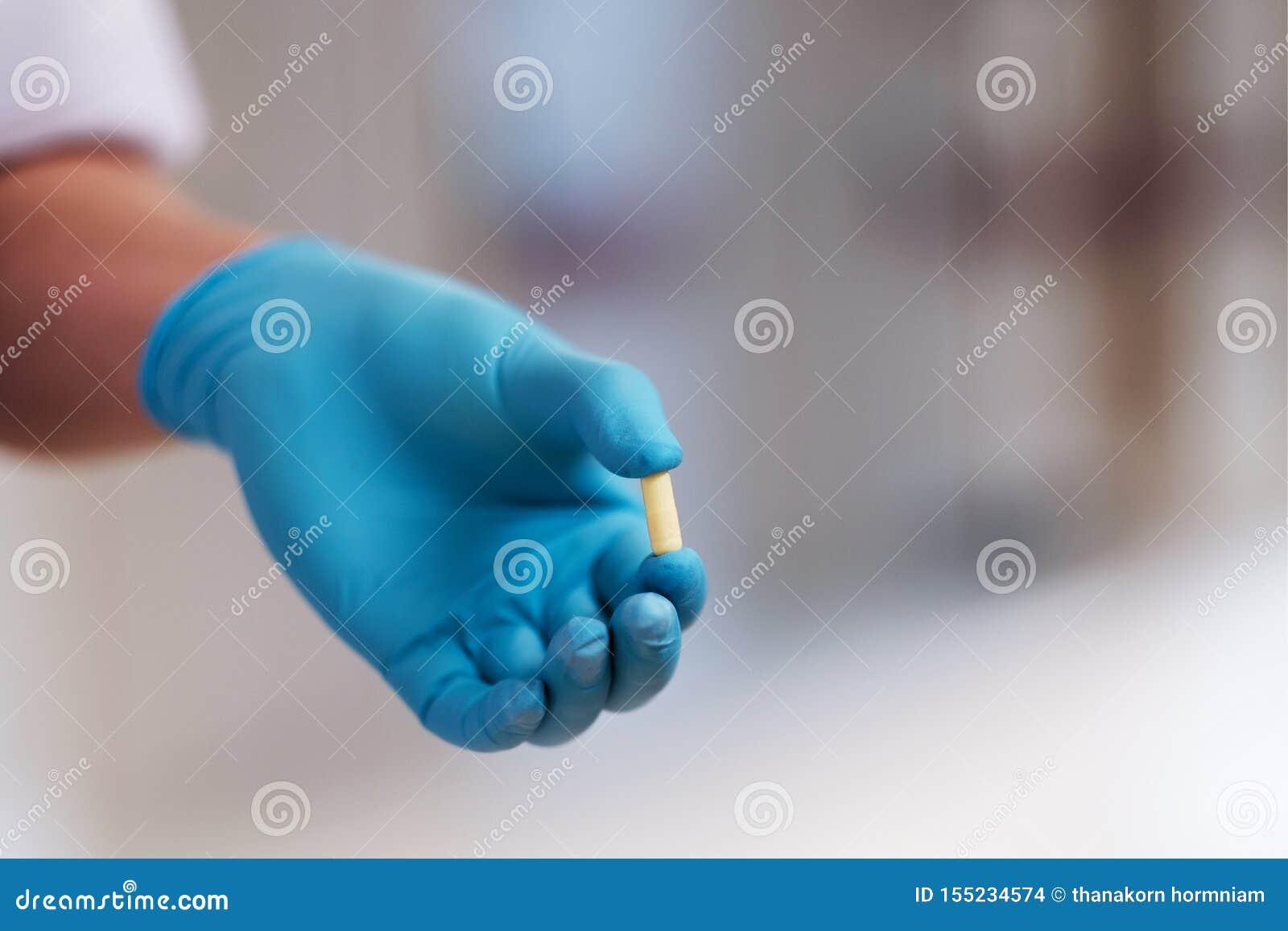 Der Doktor trägt die blauen Handschuhe und hält gelbe Kapseln