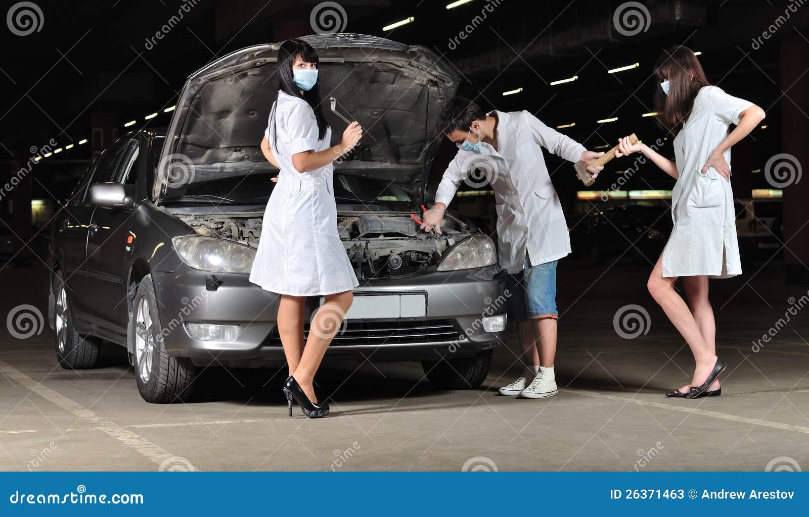 Der Doktor und die Krankenschwestern reparieren das Auto