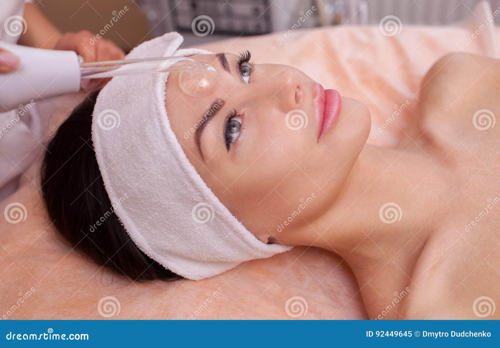 Der DoktorCosmetologist macht die Verfahren Microcurrent-Therapie von der Gesichtshaut auf der Stirn