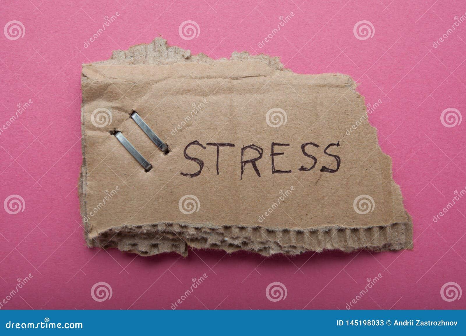 Der Drücke des Wortes ', die auf eine alte heftige Pappe geschrieben werden, wird auf einem rosa Hintergrund lokalisiert