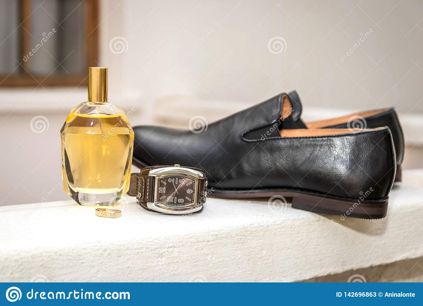 Der Ehering des Bräutigams, Parfüm, Uhr und schwarzer Lederschuh
