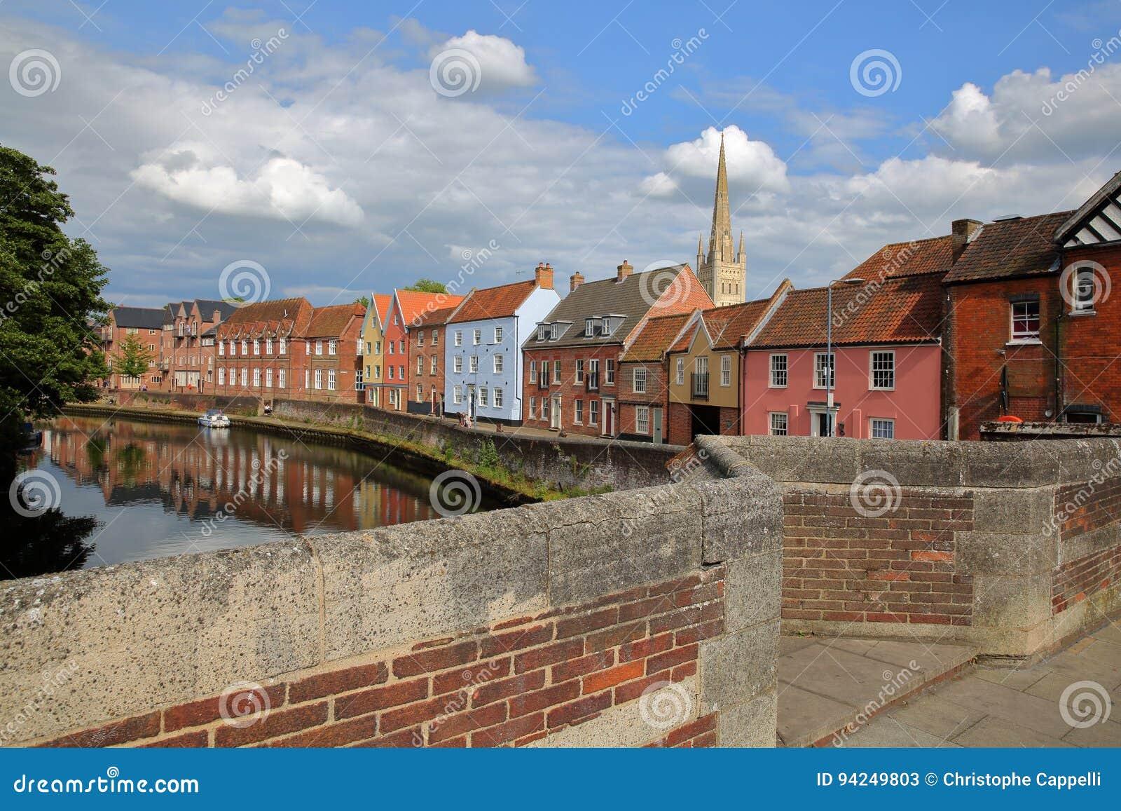 Der Flussuferfluß Wensum in Norwich Norfolk, Großbritannien mit bunten Häusern und dem Turm und Helm der Kathedrale im backgro