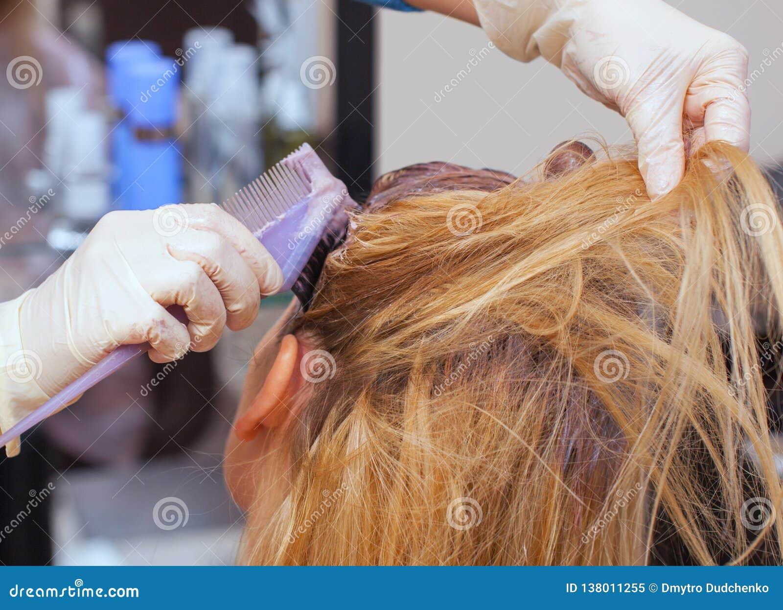 Der Friseur malt das Frau ` s Haar im Weiß, zutreffen die Farbe auf ihr Haar im Schönheitssalon