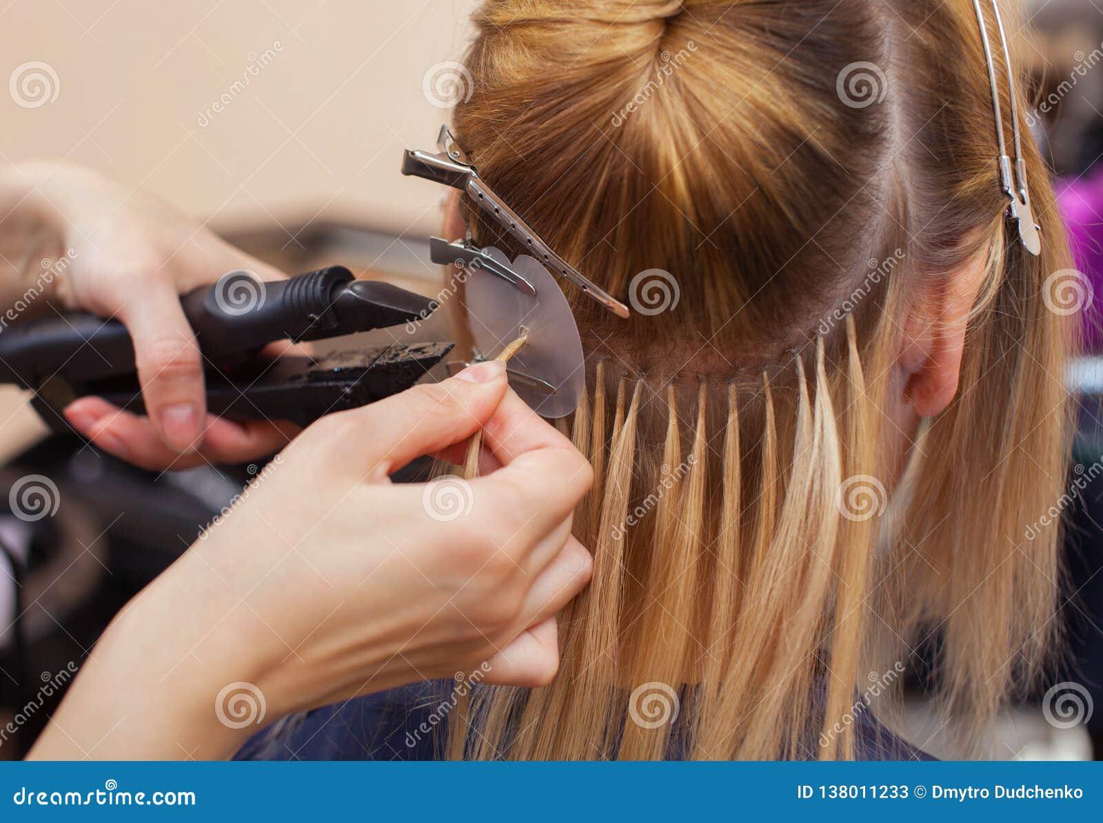 Der Friseur tut Haarerweiterungen ein junges Mädchen, eine Blondine in einem Schönheitssalon an