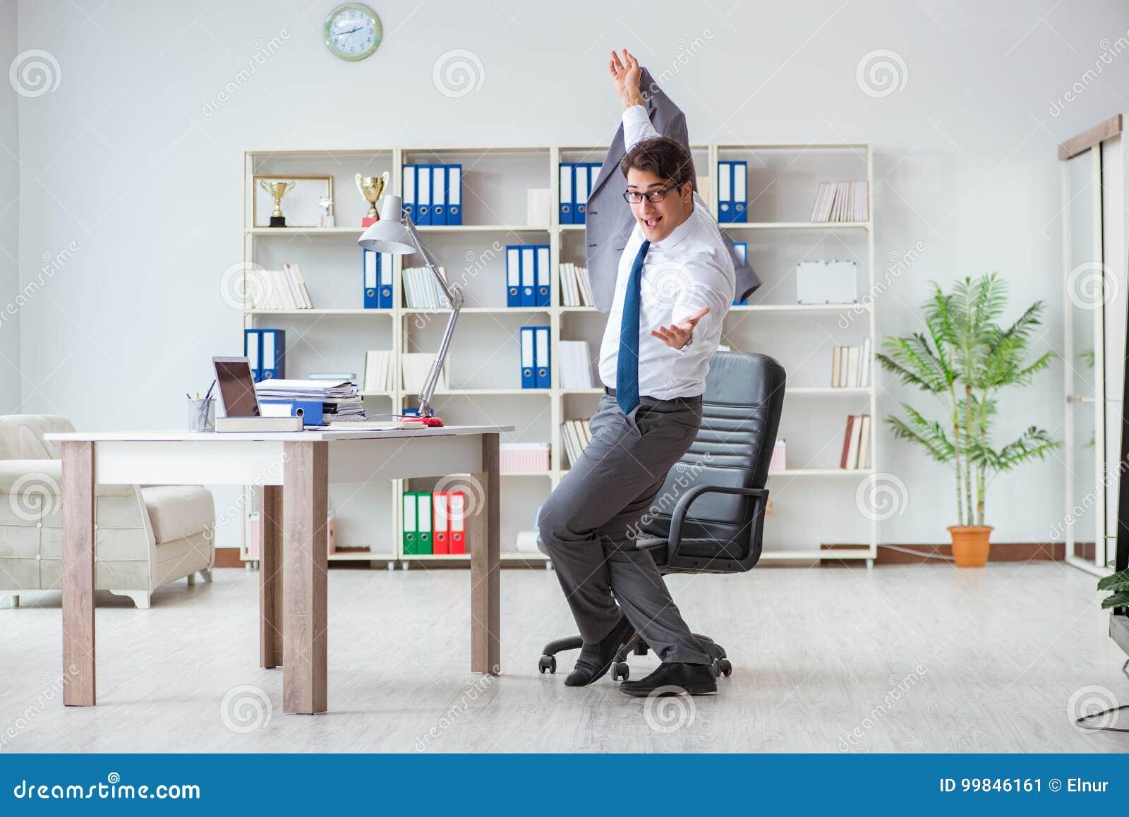 Der Geschäftsmann, der den Spaß macht eine Pause im Büro bei der Arbeit hat