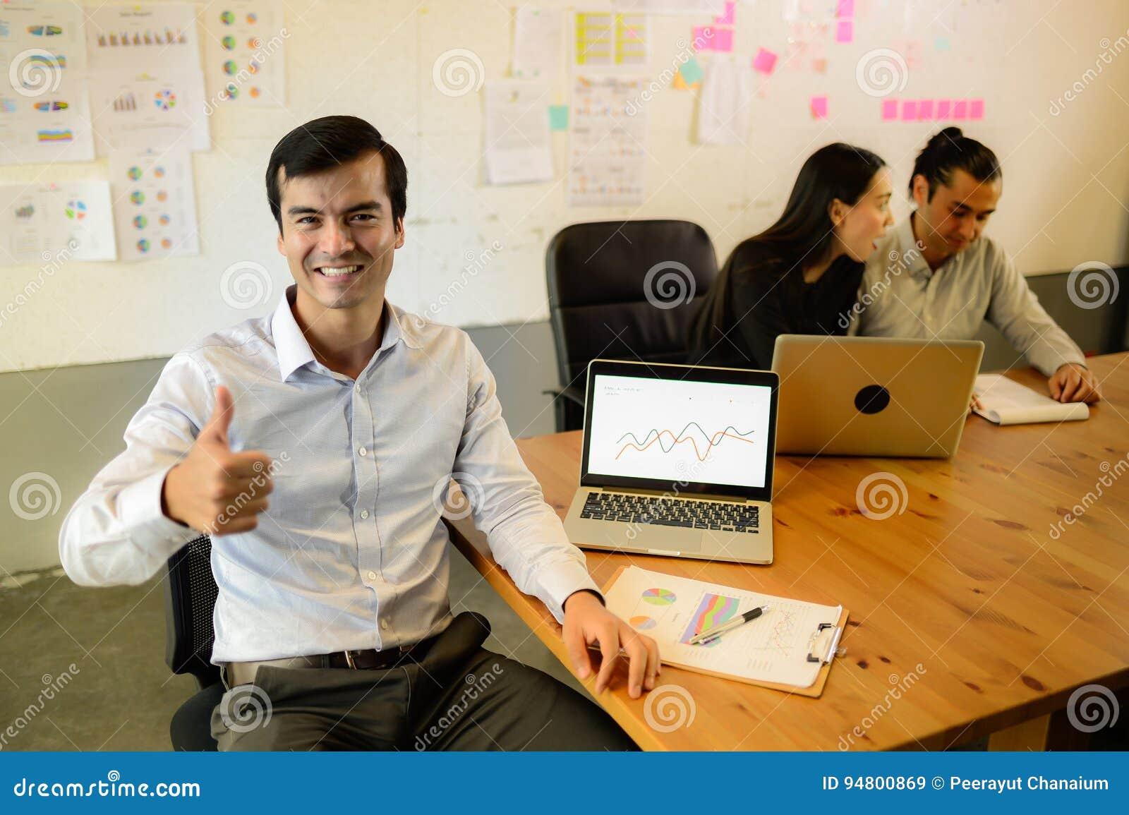 Der hübsche hohe und lächelnde Geschäftsmanndaumen, sitzt er auf dem Stuhl im Büro, erfolgreiches Konzept
