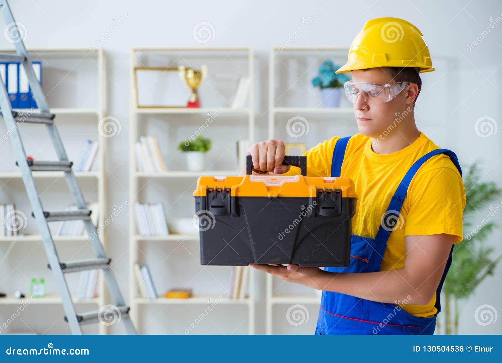 Der junge Auftragnehmer, der Reparatur tut, arbeitet im Büro
