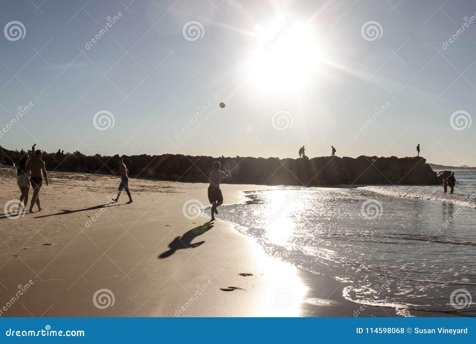 Der Junge, der Ball am Strand spielen, während andere Leute vorbei schlendern oder die Fische oder klettern den Rock am späten Na