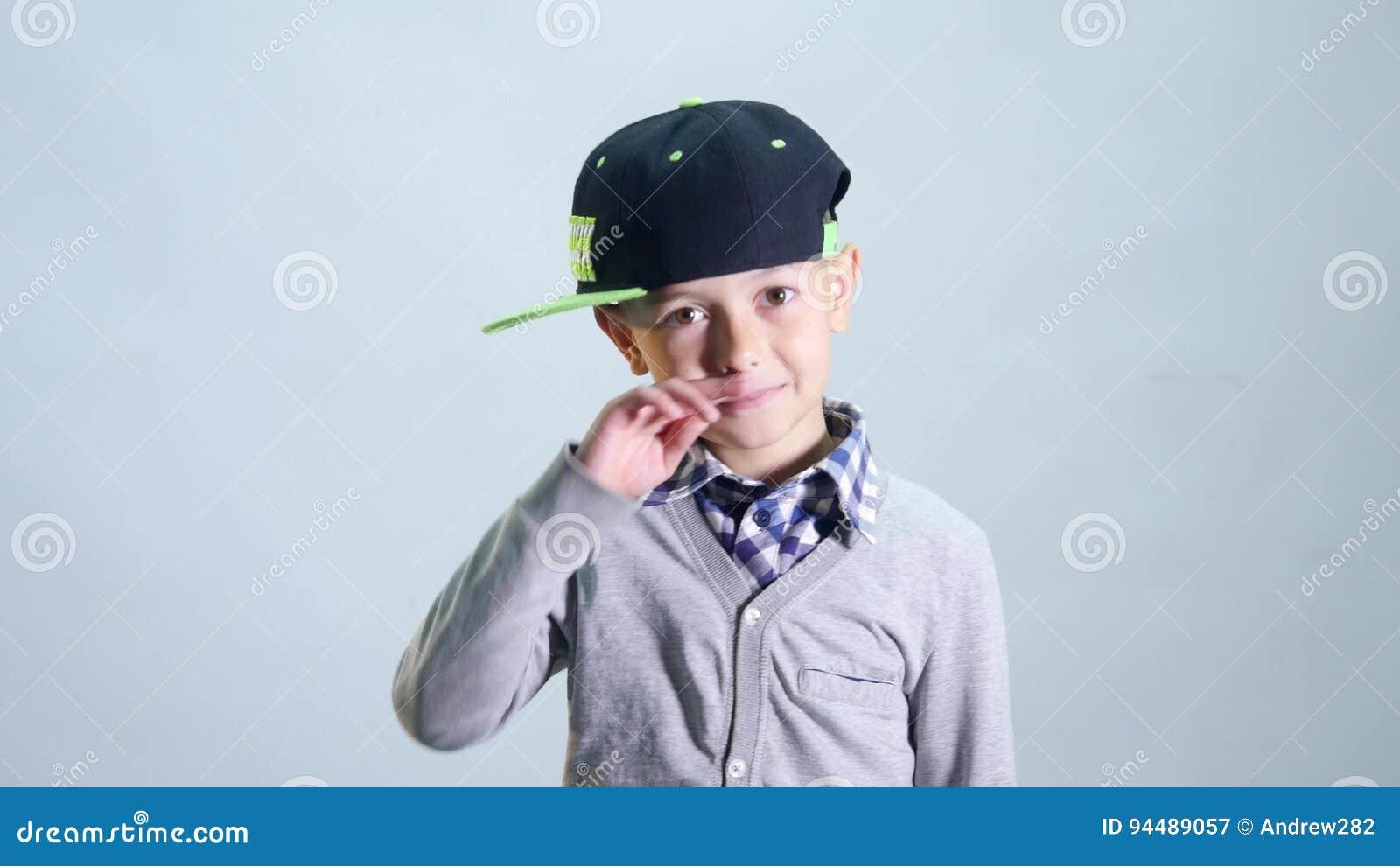 Der Junge in der Kappe wischt seine Nase mit seinem Ärmel und Sprung ab stock video
