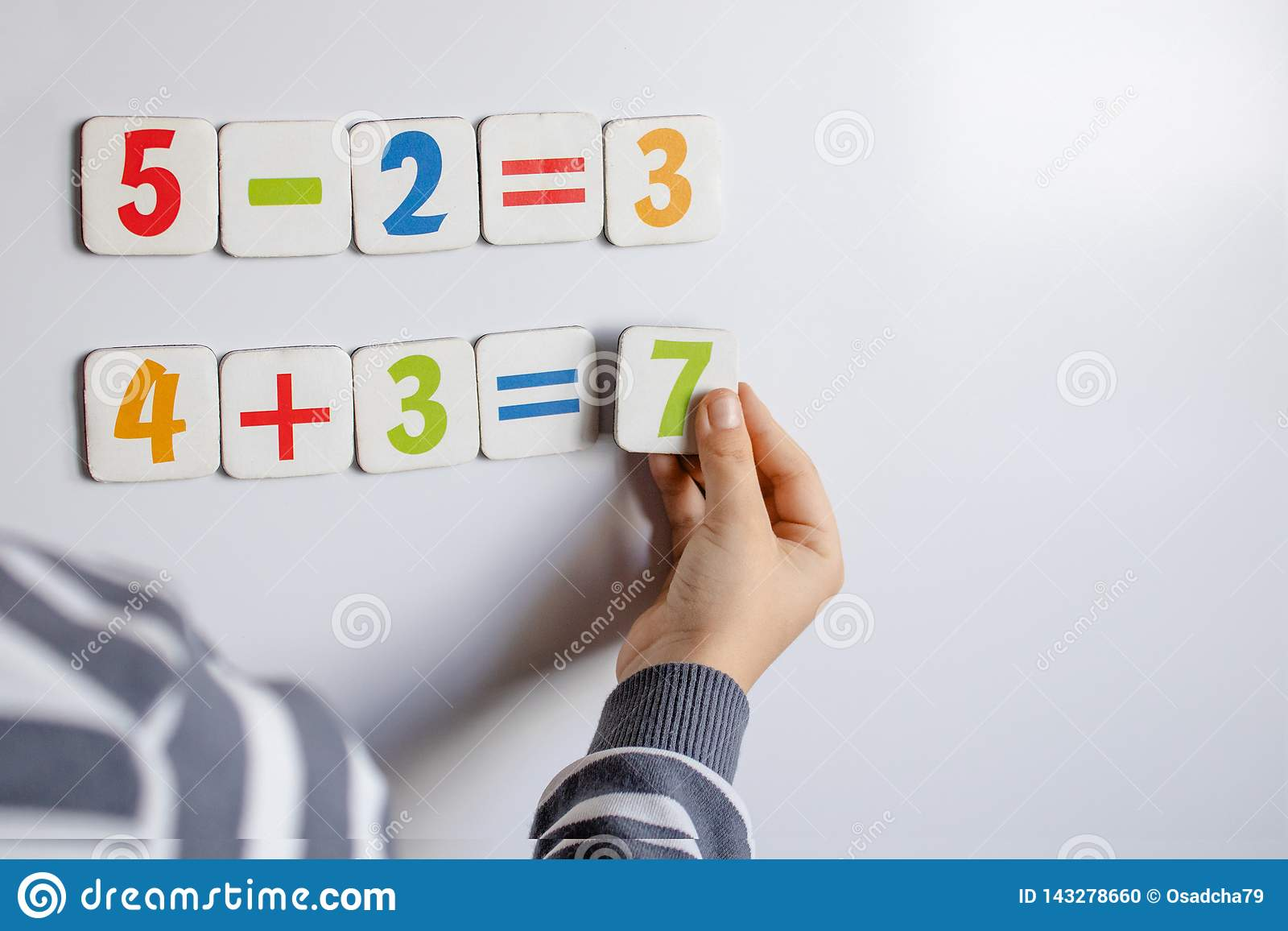 Der Junge löst mathematische Beispiele Ein Kind löst Beispiele auf einer Tafel