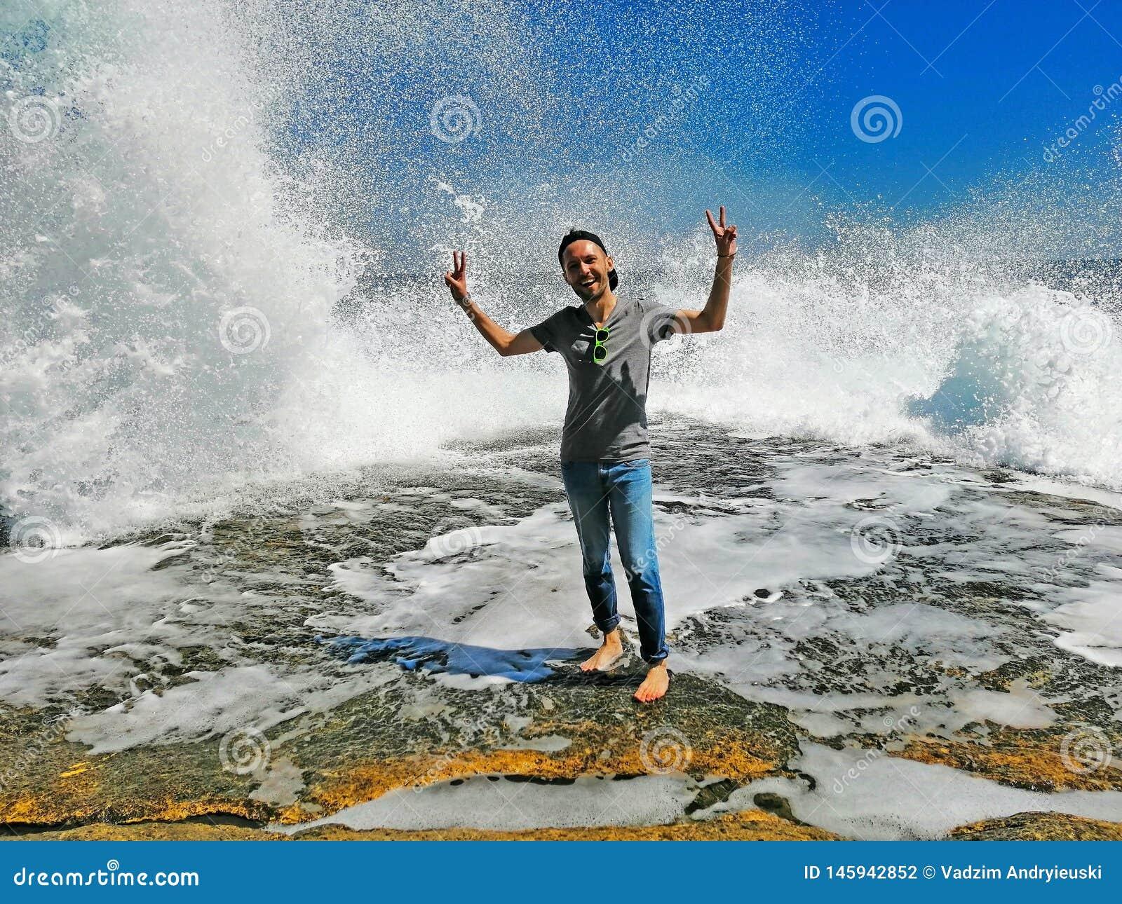 Der junge Mann, der hohe Wellen mit genießt, spritzt