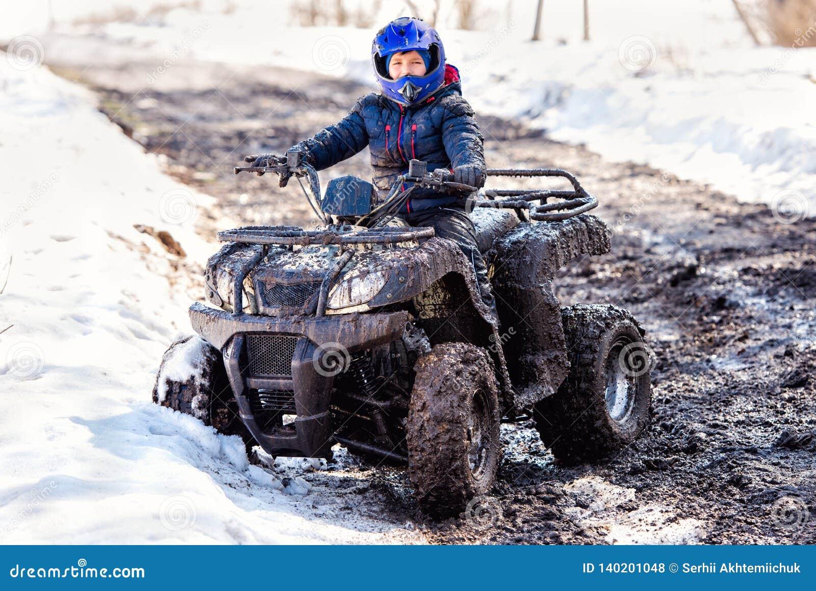 Der Junge reitet ein ATV nicht für den Straßenverkehr