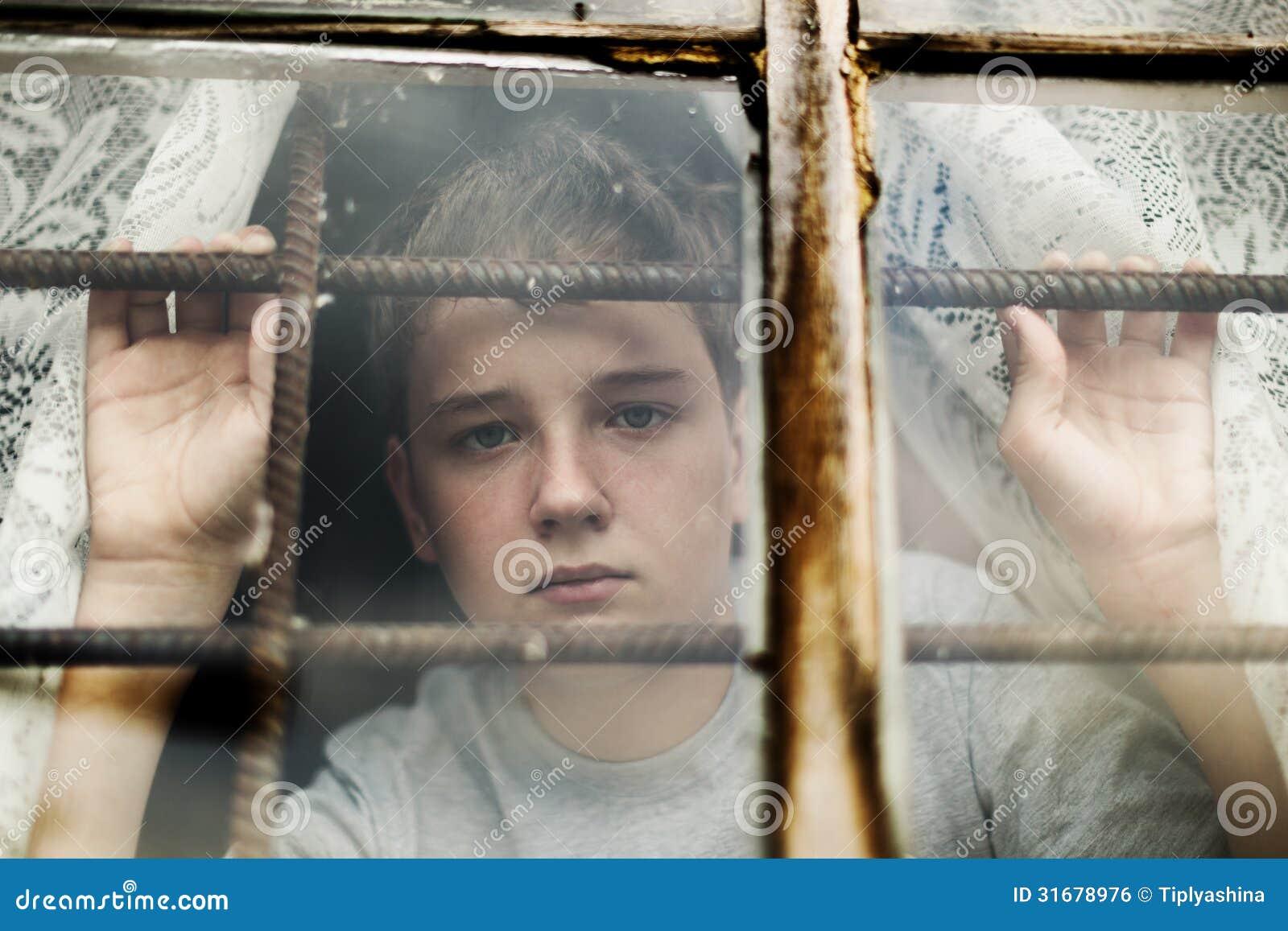 Der Junge schaut aus dem Fenster heraus durch ein Gitter