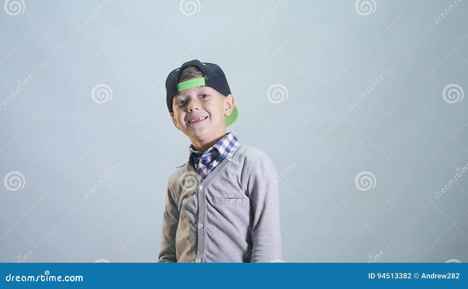 Der Junge setzt an die Kappe und zeigt die Klasse, die auf weißem Hintergrund lokalisiert wird stock video footage