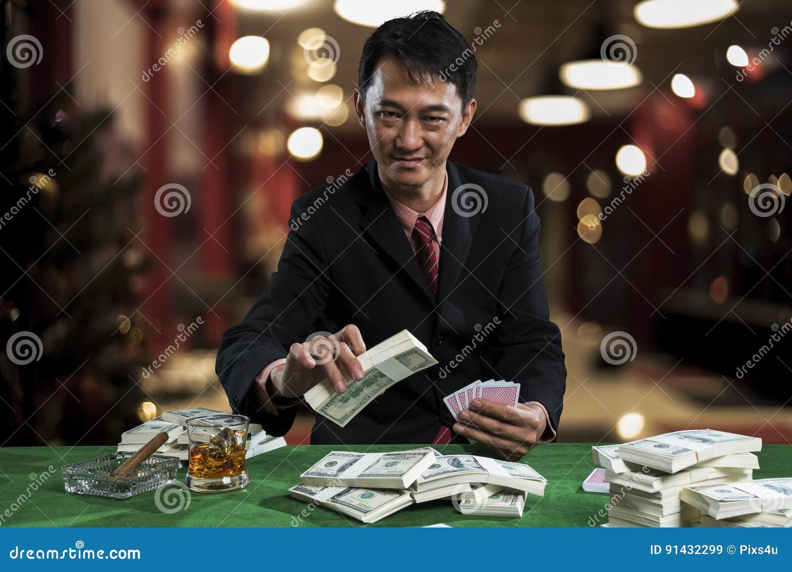 Der junge Spieler setzt Wetten in die Stapel der Banknote