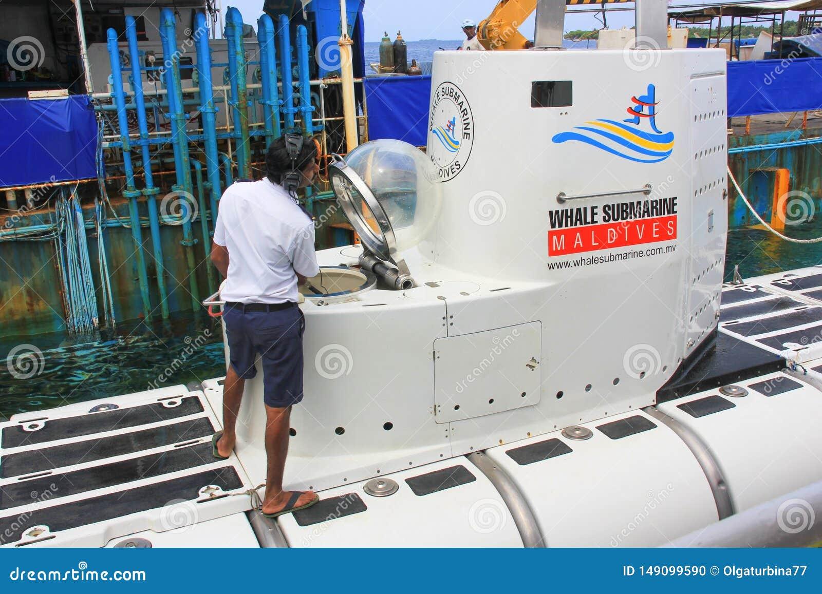 Der Kapit?n des touristischen wei?en Unterseeboots im Hafen des Mannes macht eine letzte Inspektion vor der Immersion