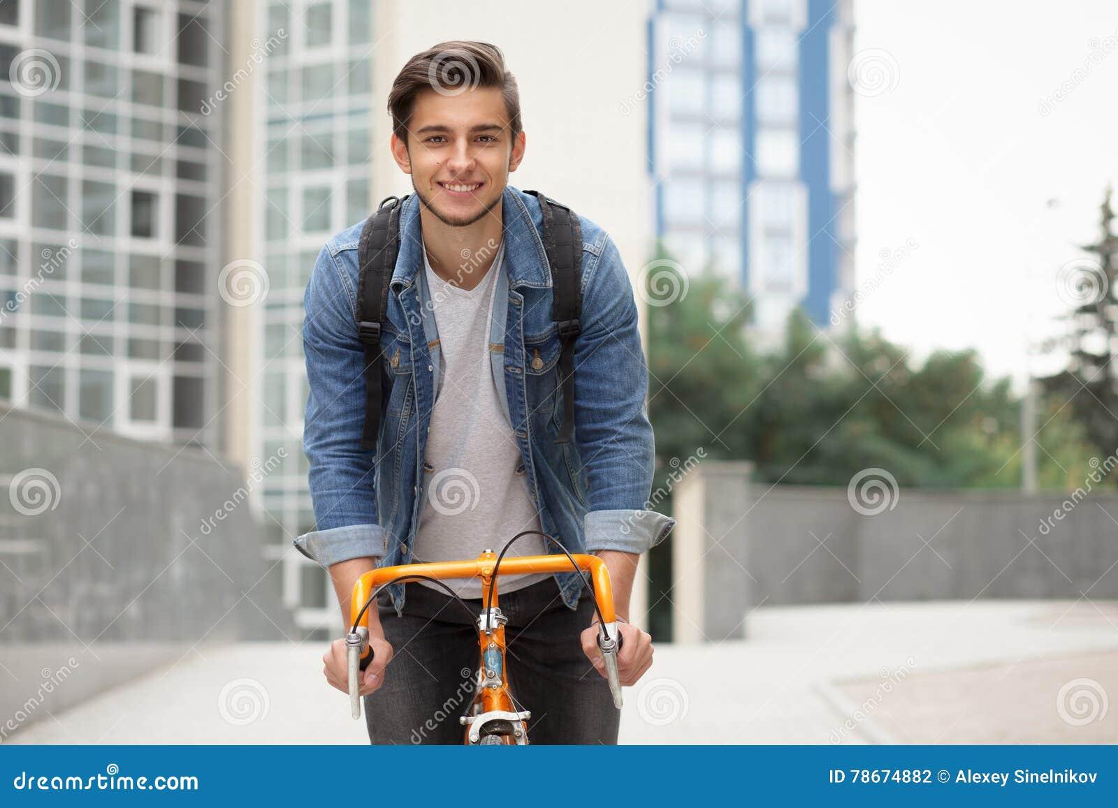 Der Kerl geht zur Stadt auf einem Fahrrad in der Blue Jeans-Jacke junger Mann ein orange Verlegenheitsfahrrad
