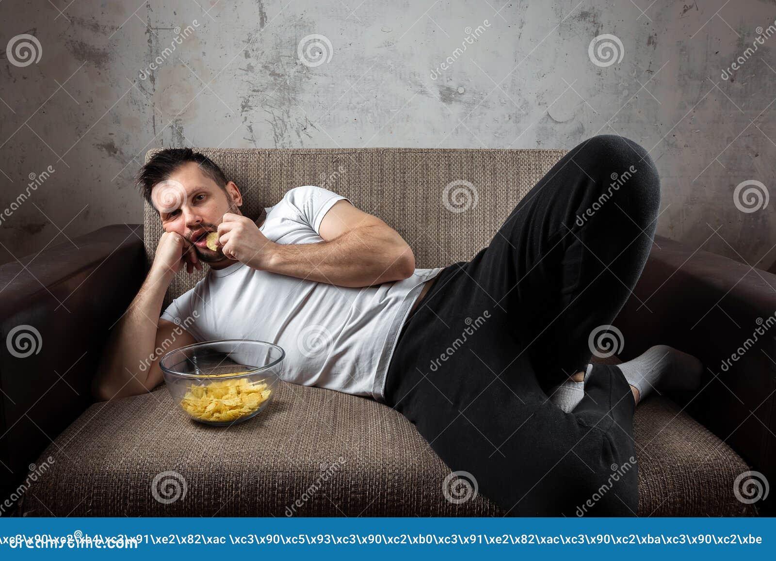 Der Kerl im Hemd liegt auf der Couch, isst Chips und passt einen Sportkanal auf Das Konzept der Tr?gheit