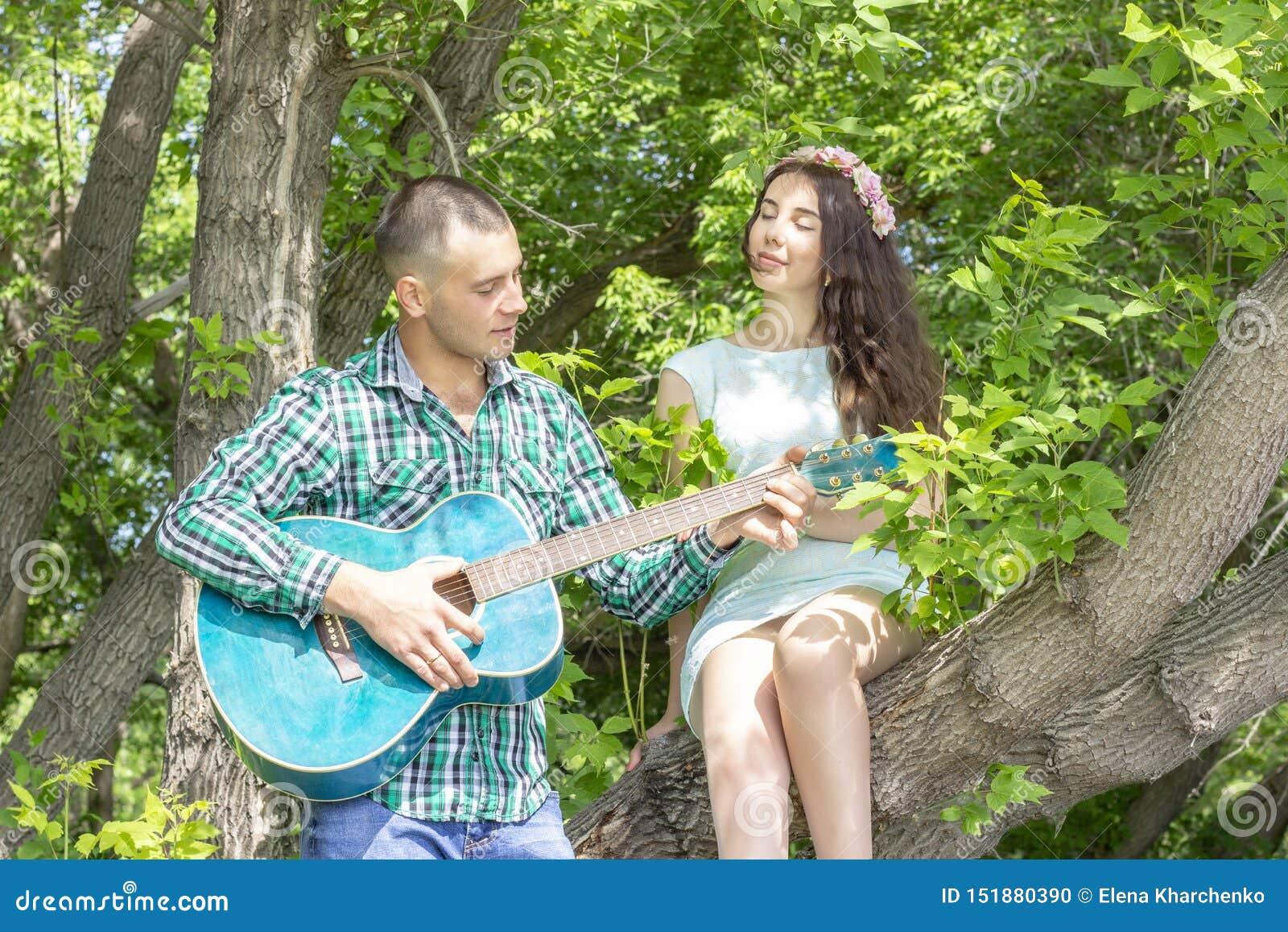 Der Kerl spielt seine geliebte Gitarre Mädchen mit Vergnügen mit geschlossenen Augen hören, sitzend auf einem Baum