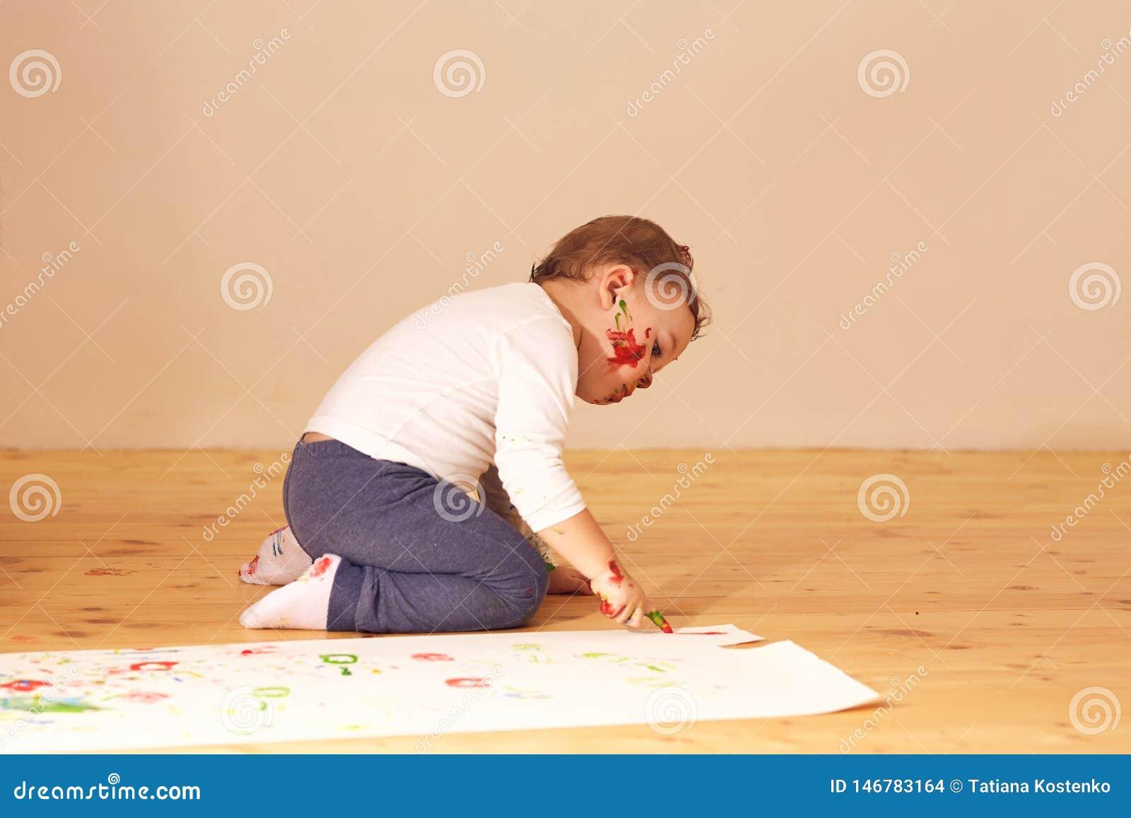 Der kleine Junge, der in der Hauptkleidung gekleidet wird, sitzen auf dem Bretterboden im Raum und malen mit den Fingern auf dem