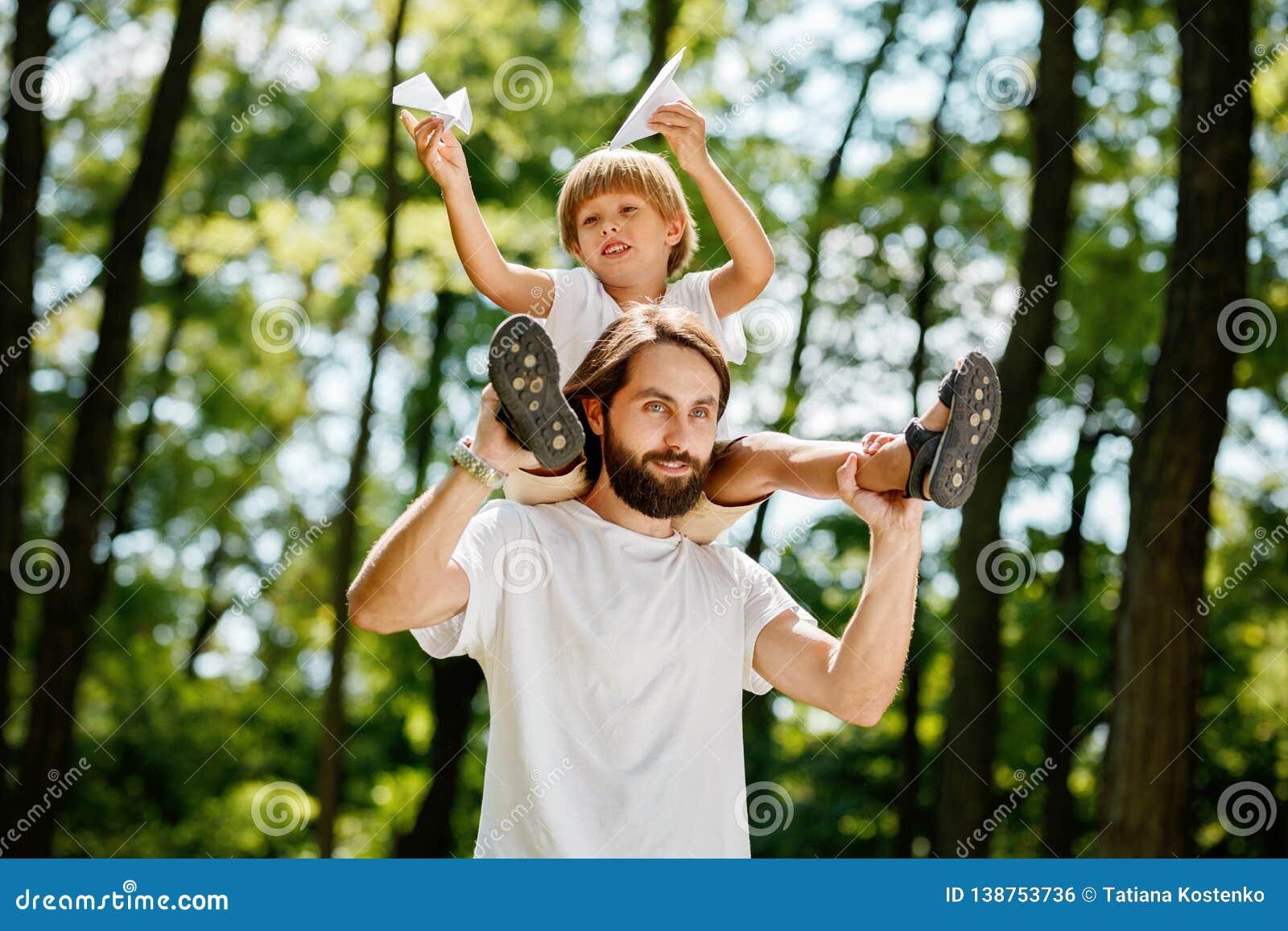 Der kleine Junge mit seinem Vater, der in den weißen T-Shirts gehend in den Waldjungen gekleidet wird, sitzt auf den Schultern vo