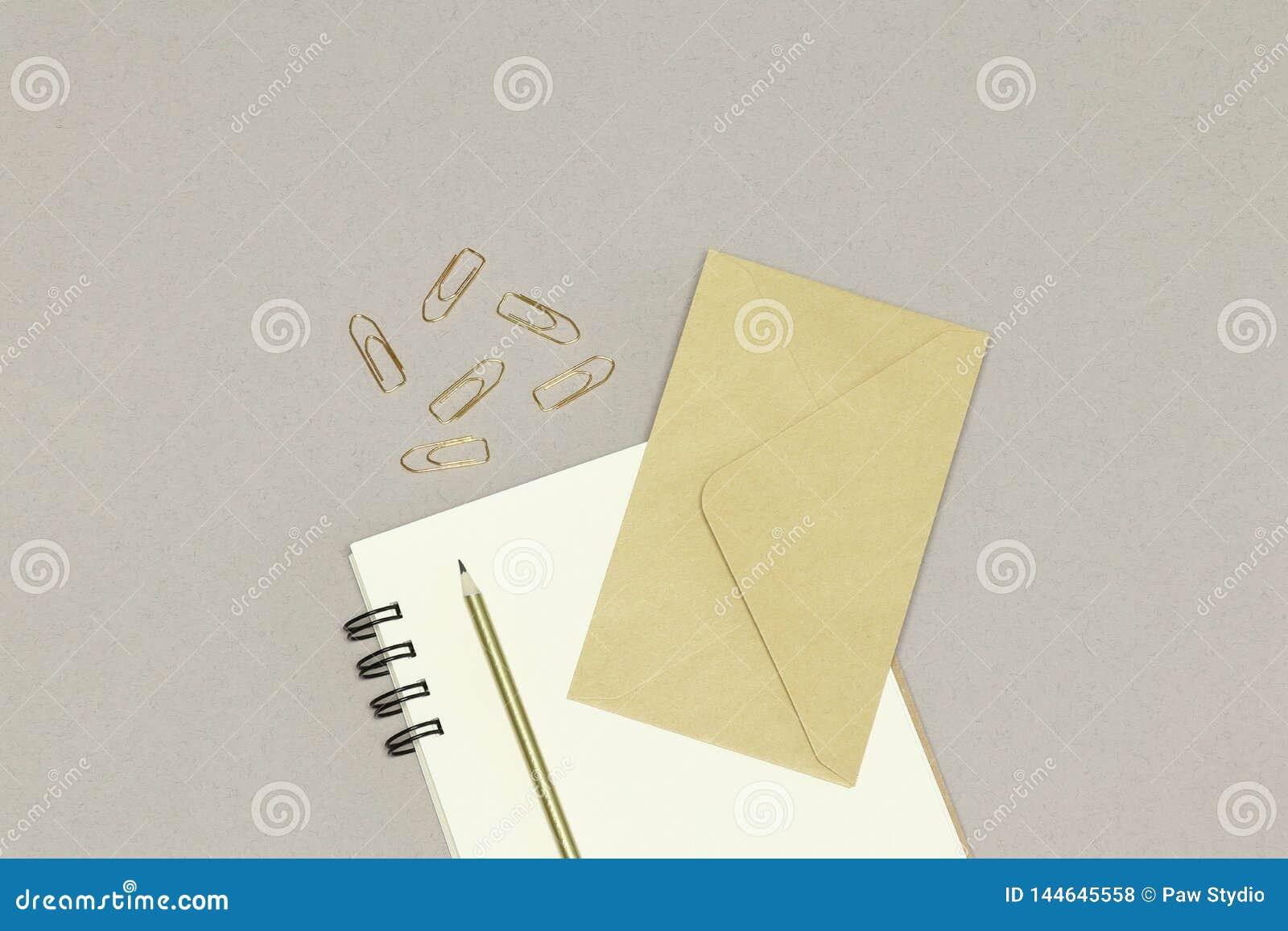 Der Kraftpapier-Umschlag, die Anmerkungen, der goldene Bleistift u. die Büroklammern, auf dem weißen Hintergrund