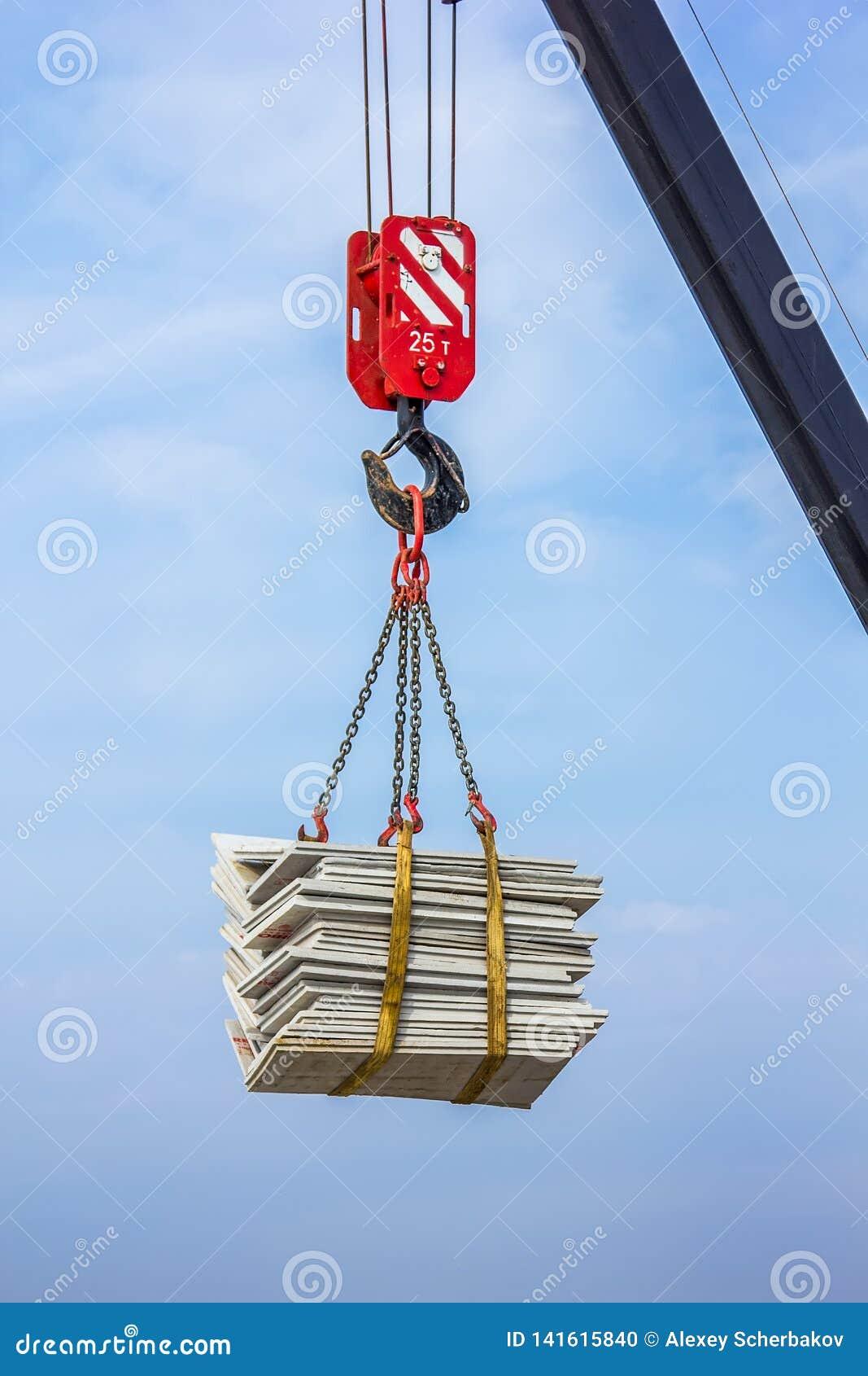 Der Kran hebt eine schwere Last auf einem Haken an