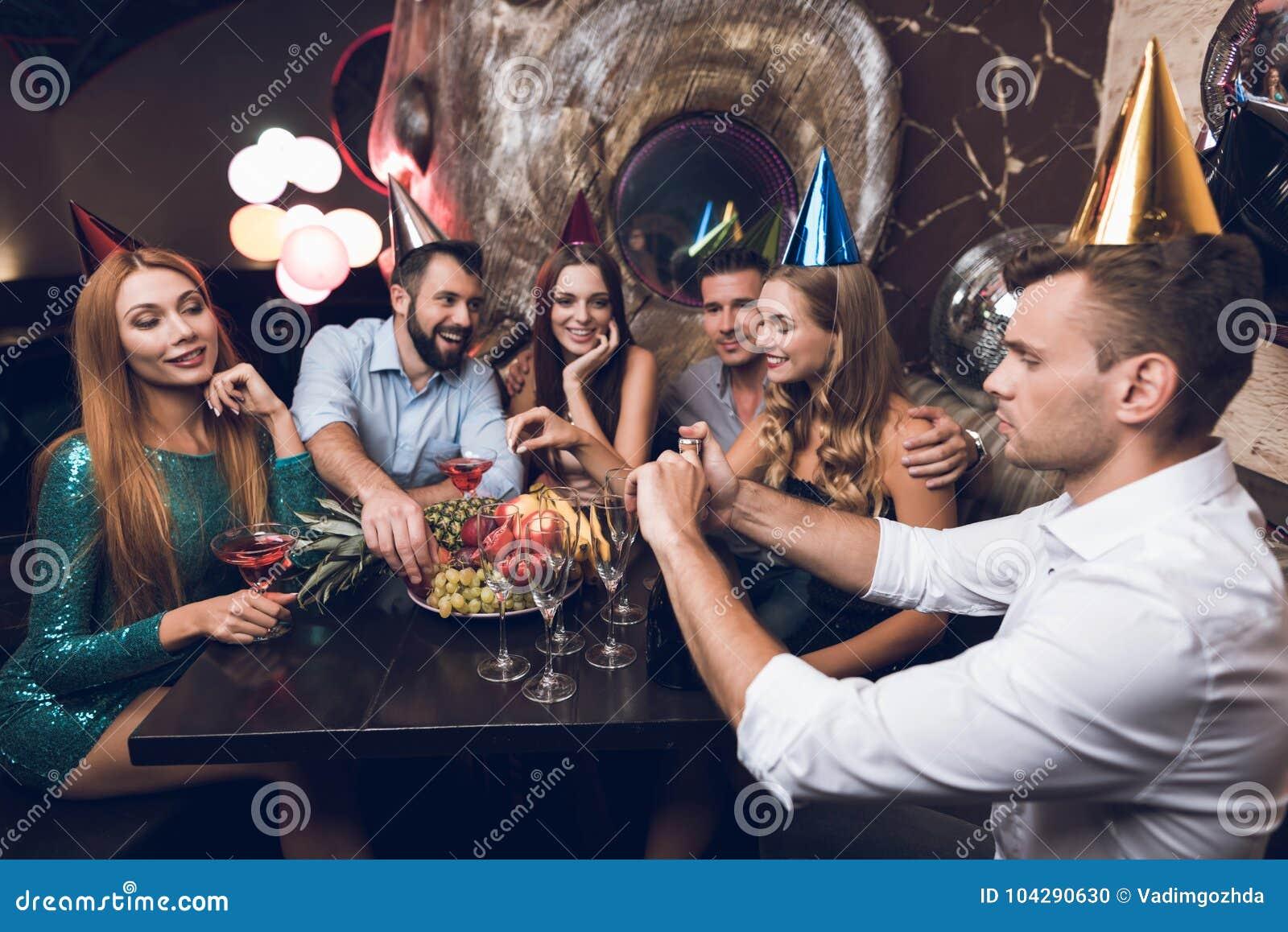 Der Mann öffnet Champagner zum Getränk mit seinen Freunden Sie sitzen im Verein am Tisch und im Rest nach dem Tanz
