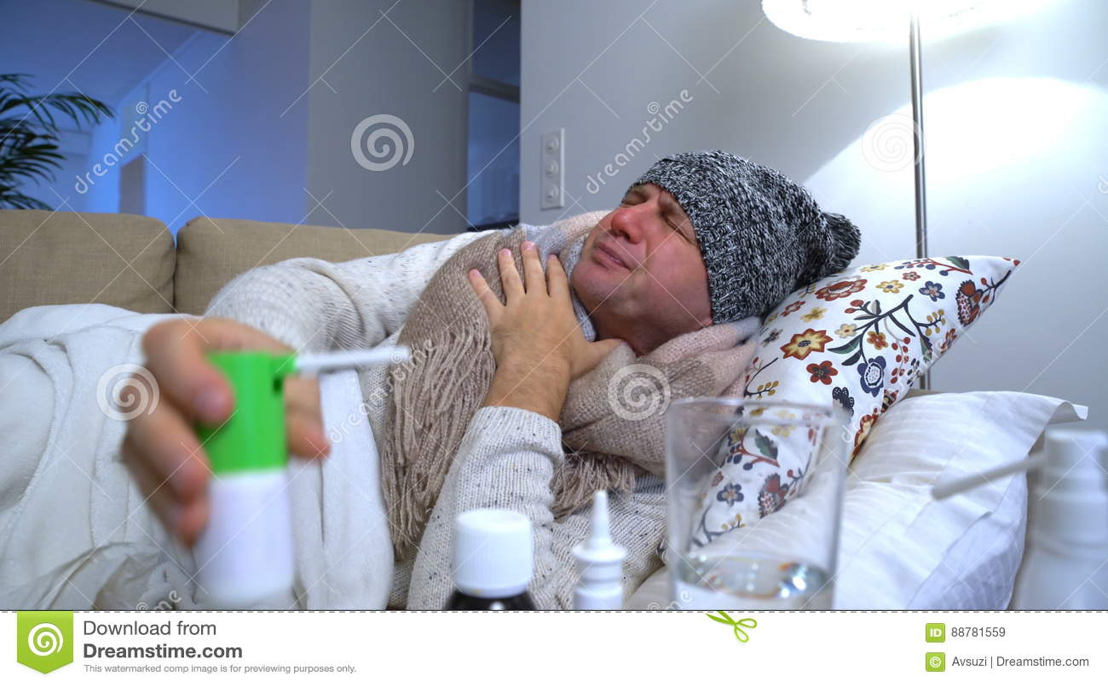 Der Mann, der eine warme Kappe und einen Schal in einem Bett trägt, hustet und benutzt Spray für Kehle stock footage