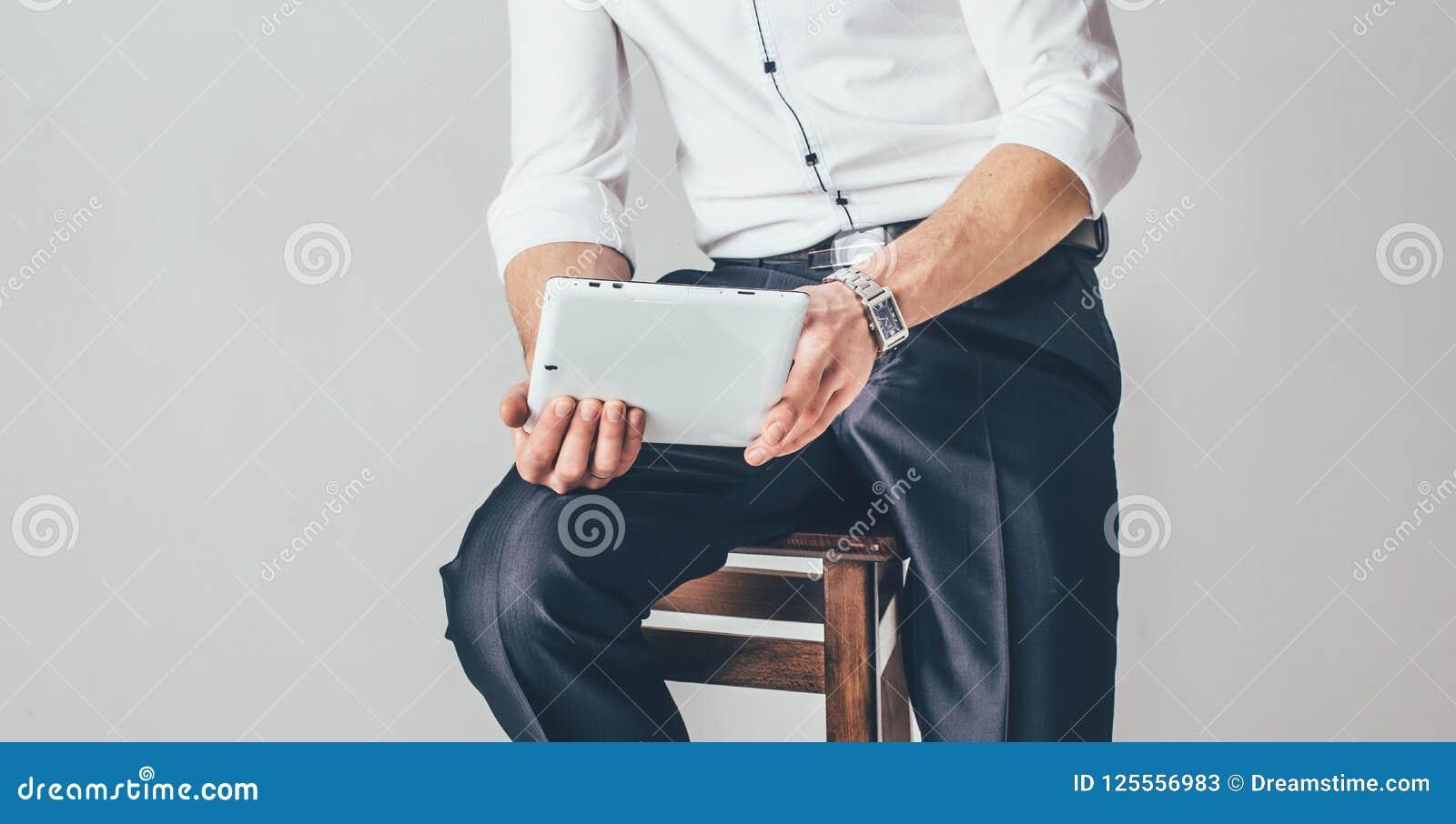 Der Mann hält eine Tablette in seinen Händen auf dem weißen Hintergrund Er sitzt auf einem Stuhl, der in einem schicken weißen He