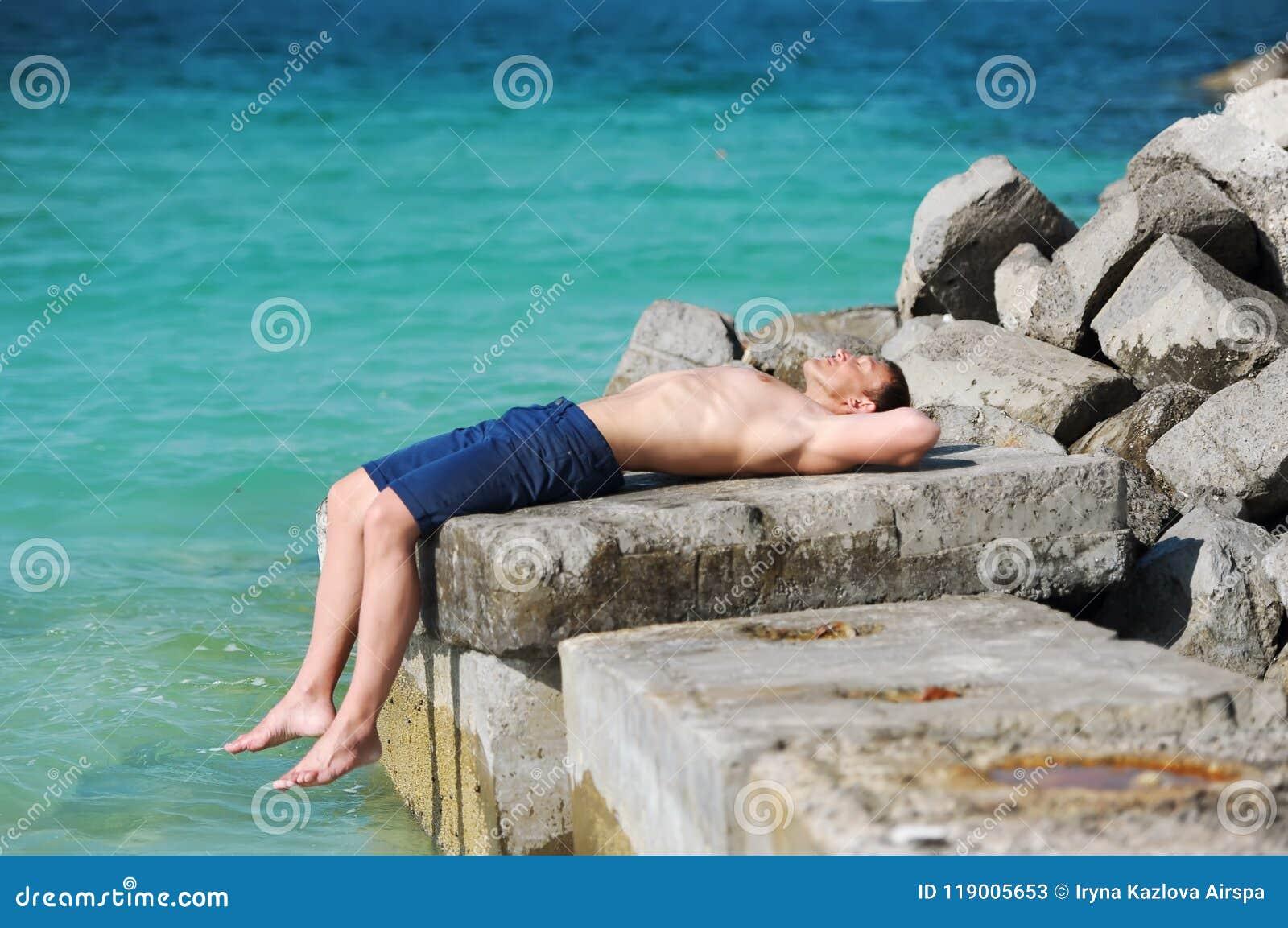 Der Mann mit einem nackten Torso, der auf einem Stein vor dem hintergrund des Meeres liegt