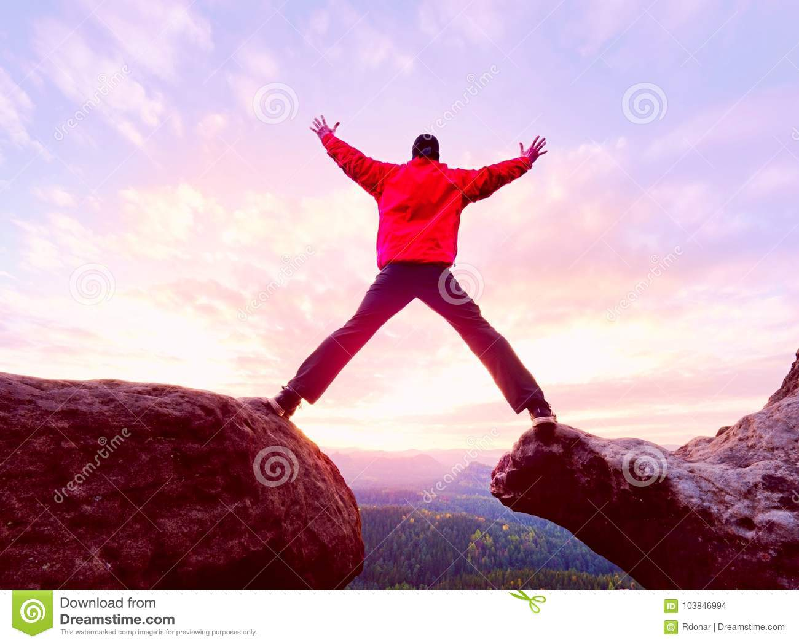 Der Mann springend vom Gebirgsrand Der Mann springend weg von einer Klippe ohne Seil Riskanter Moment