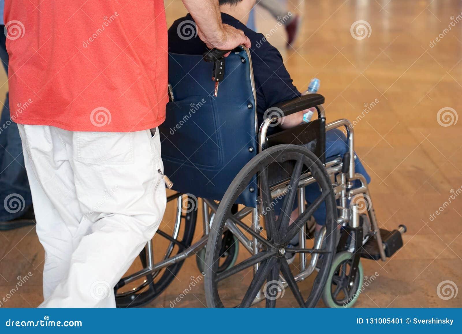 Der Mann trägt einen Behinderter in einem Rollstuhl