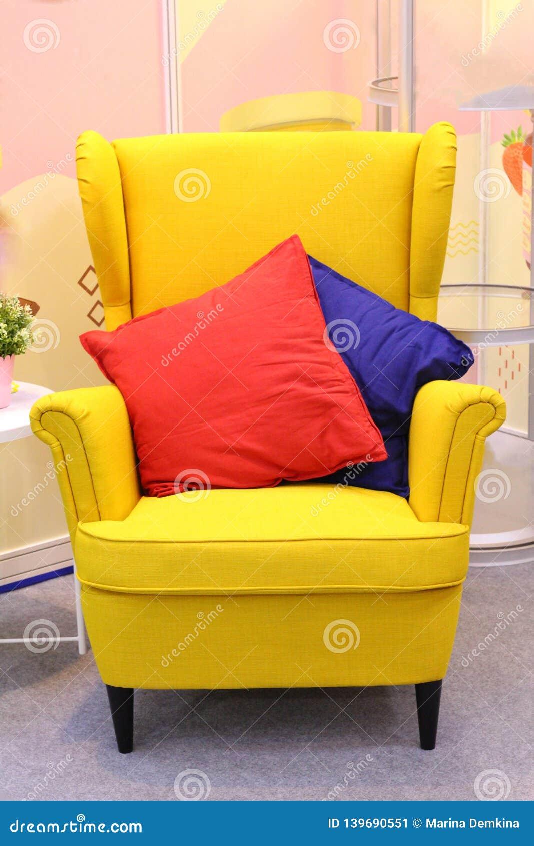 In der Mitte ist ein heller gelber Lehnsessel, mit zwei Kissen auf ihm - rot und blau