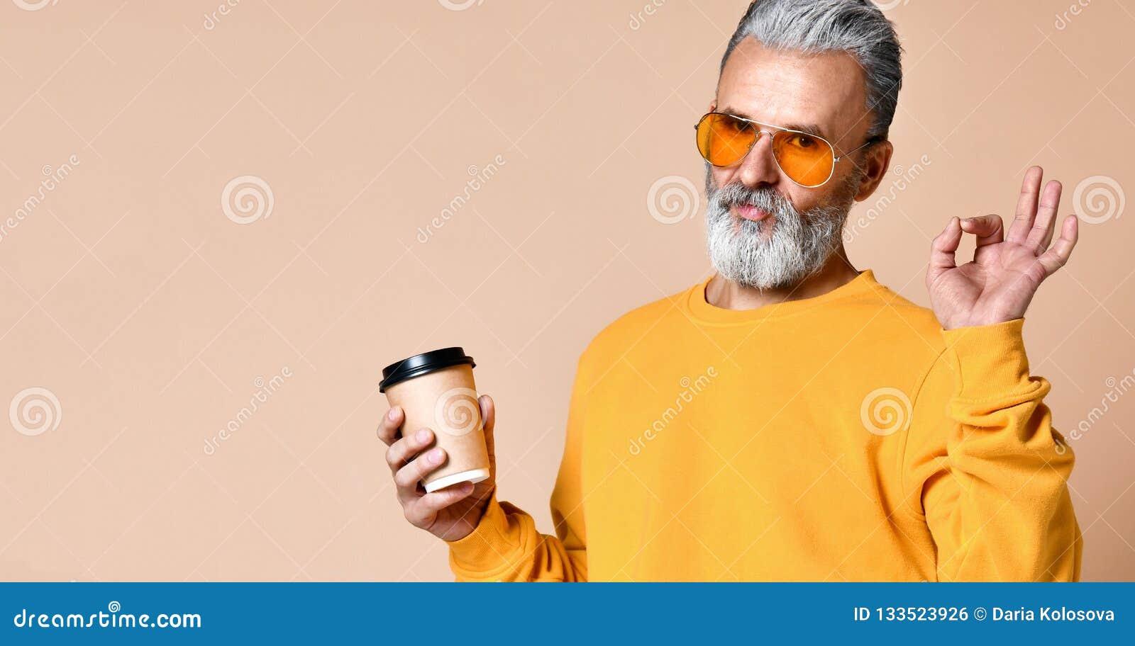 Der moderne Mannsenior, der Kamera, Kappe mit Kaffee in den Armen habend betrachtet und zeigt ein Zeichen-O.K. mit seinen Fingern