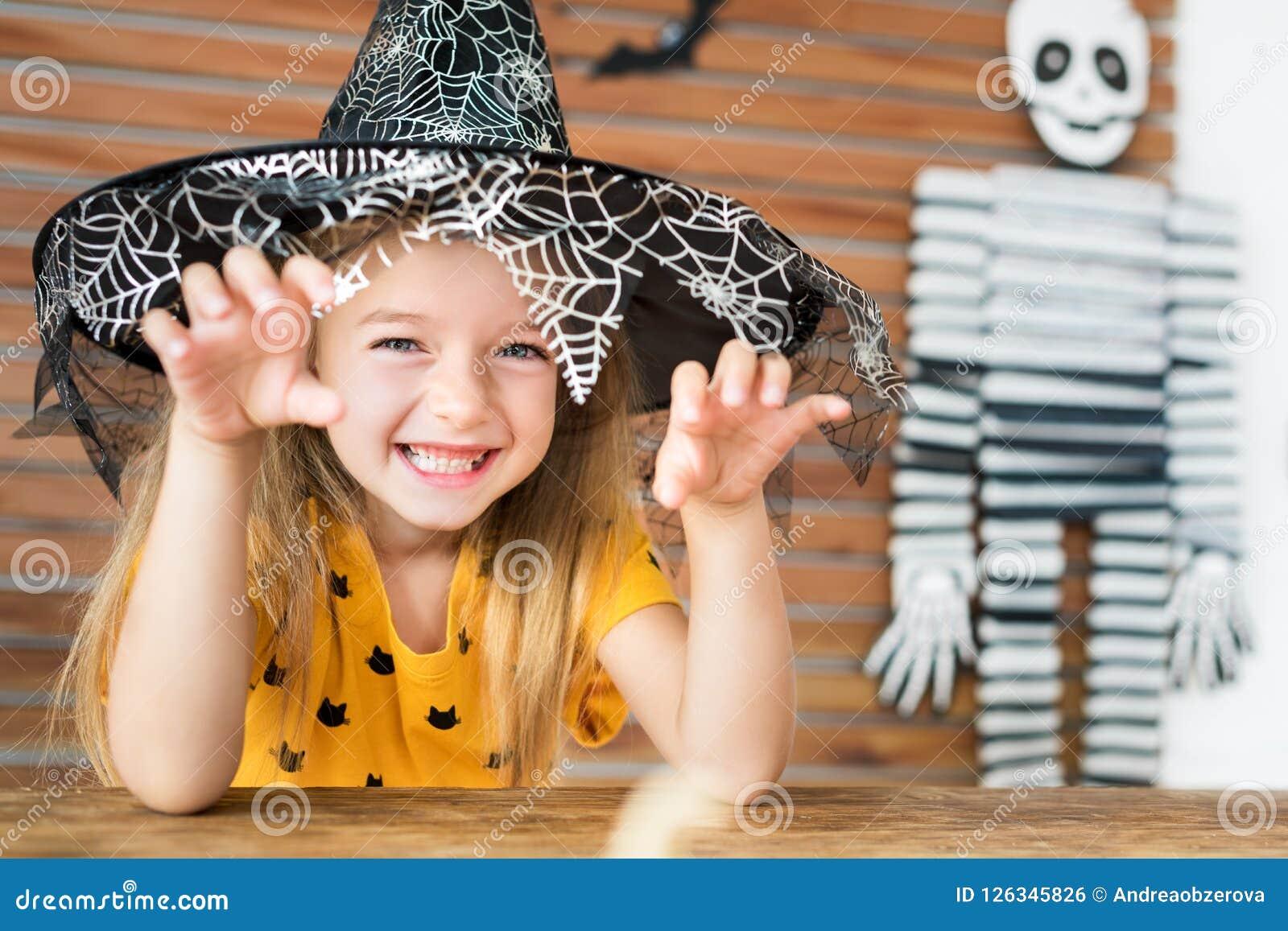 Der nette tragende Hexenhut des kleinen Mädchens, der hinter einer Tabelle in Halloween-Thema sitzt, verzierte das Wohnzimmer und