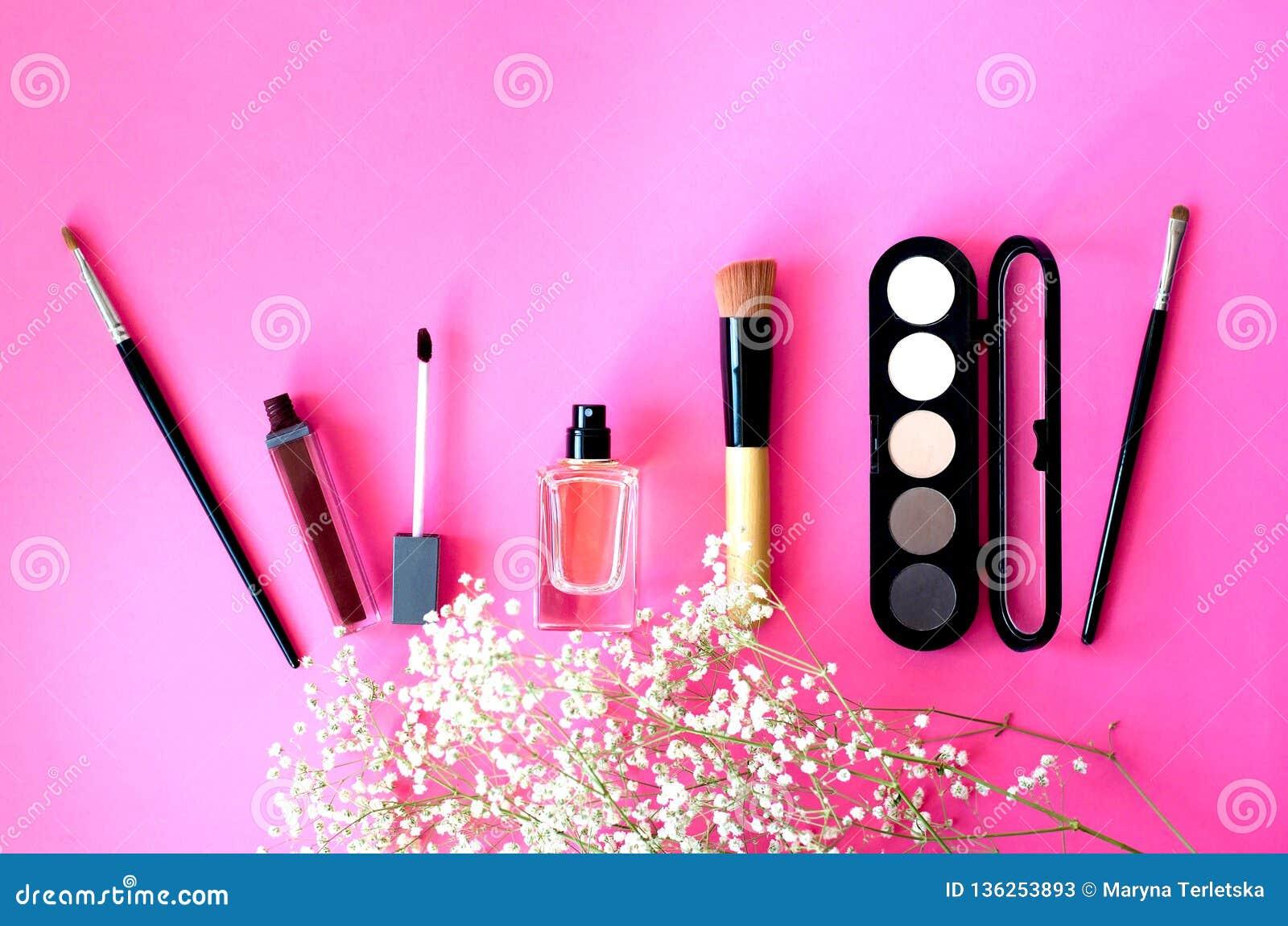 Der Plan von Kosmetik auf einem rosa Hintergrund mit einer Niederlassung einer Zierpflanze