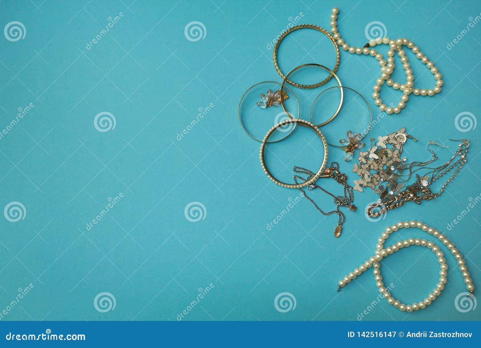 Der Schmuck und das andere Material der Frauen auf einem blauen Hintergrund