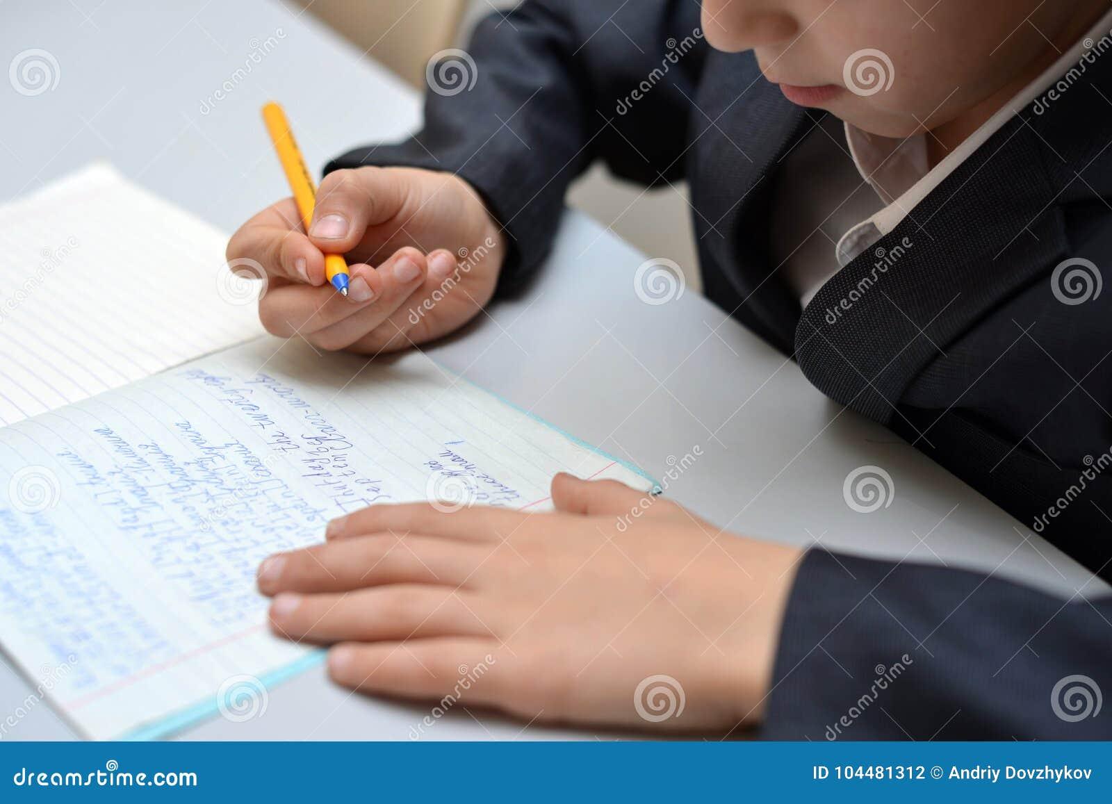 Der selektive Fokus des kleinen Jungen lernend, wie man seinen Namen, Kinderstudie zu Hause, Kinder tun Hausarbeit zu Hause, Konz