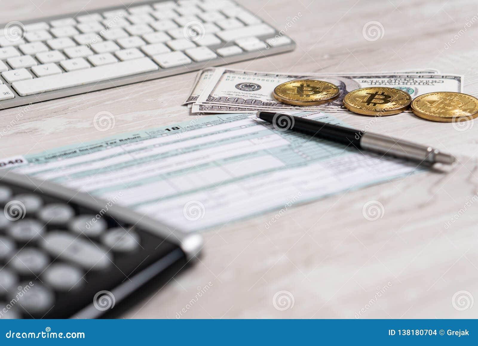Der Stift, die bitcoins, die Dollarscheine und der Taschenrechner auf dem Steuerformular U 1040 S nahe bei Computertastatur Indiv