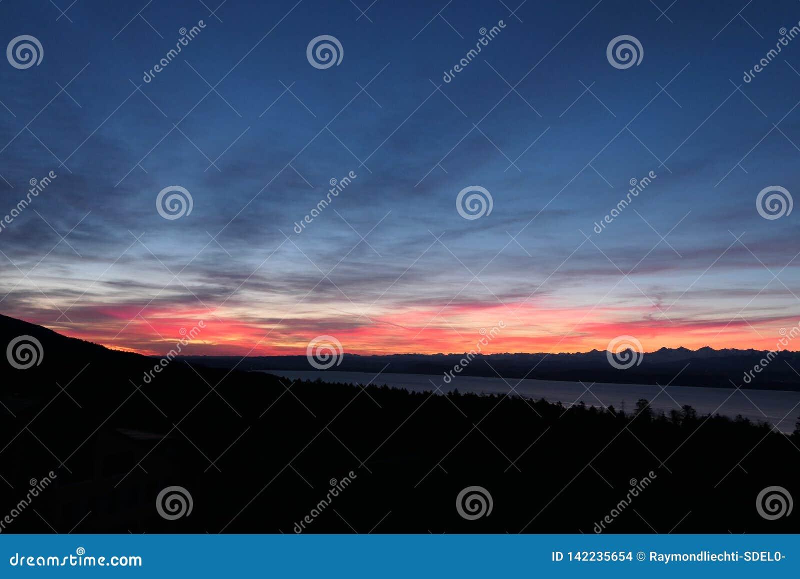 Der Tag steigt mit herrlichen Farben im Himmel und in den Schweizer Alpen im Hintergrund