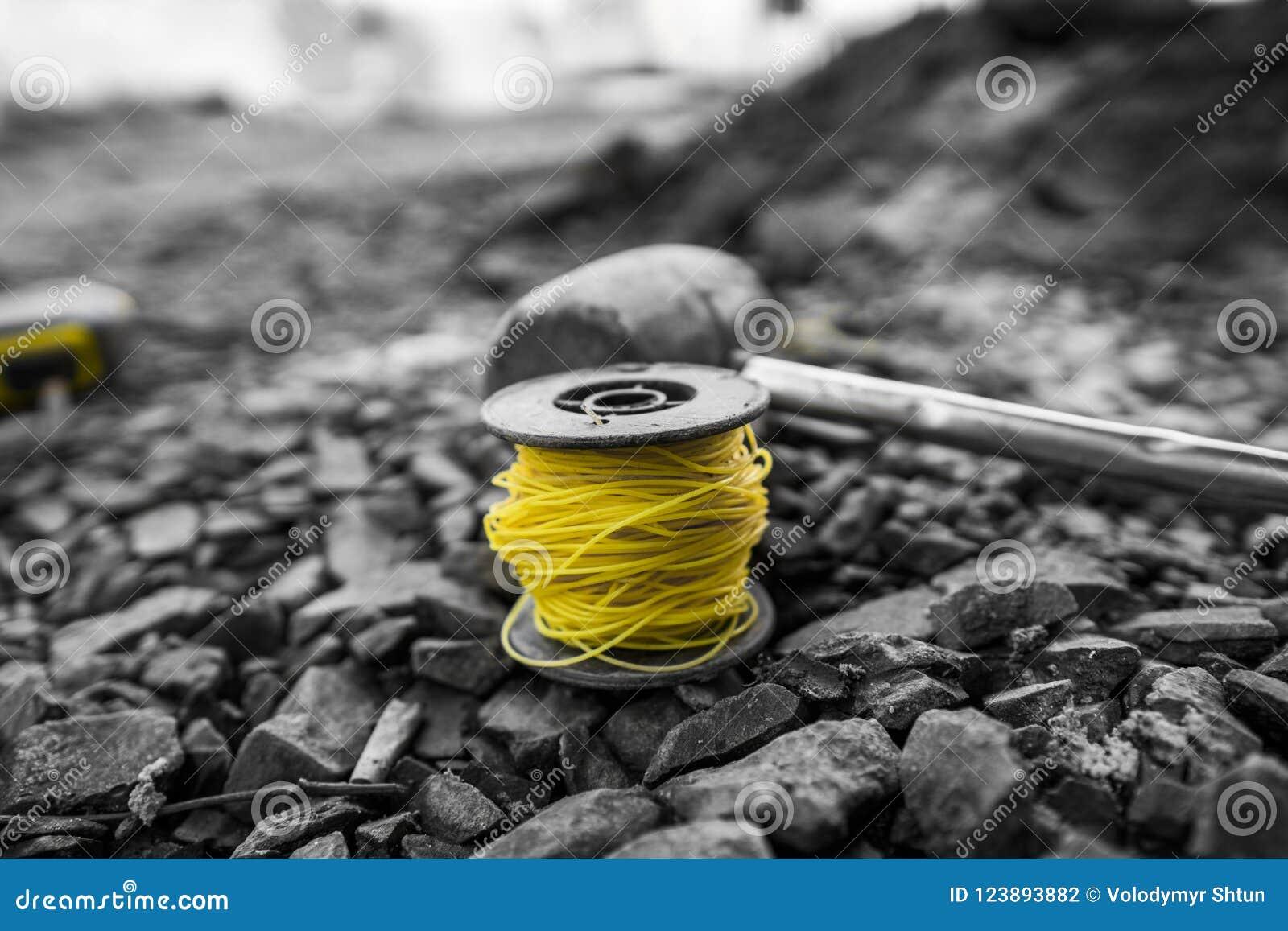 Der Thread, zum des Niveaus, vor der Platzierung des Kopfsteins, zu bestimmen und der Hammer liegen auf dem Schutt während des Bü