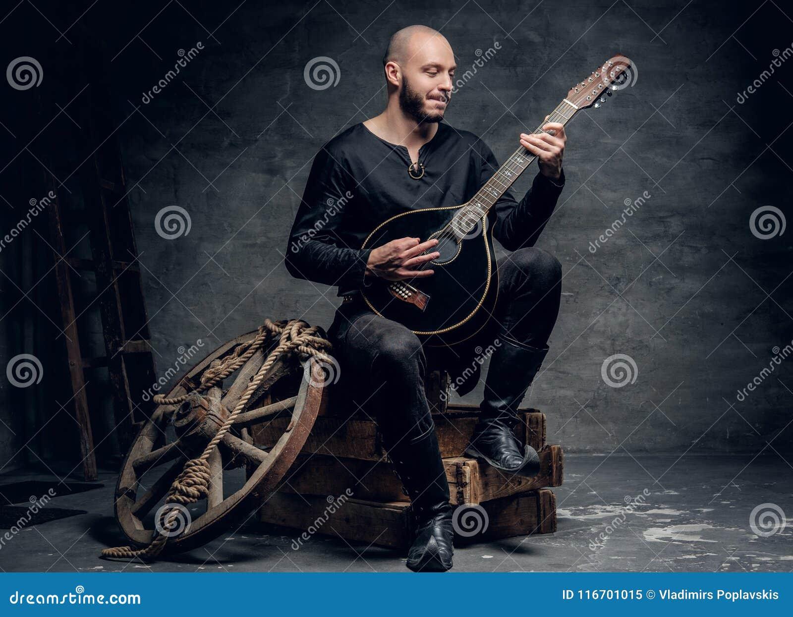 Der traditionelle Volksmusiker, der in der keltischen Kleidung der Weinlese gekleidet wird, sitzt auf einer Holzkiste und spielt