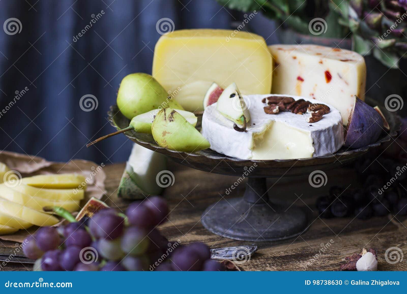 Der unterschiedliche Käse auf Metallbehälter und frischen Früchten
