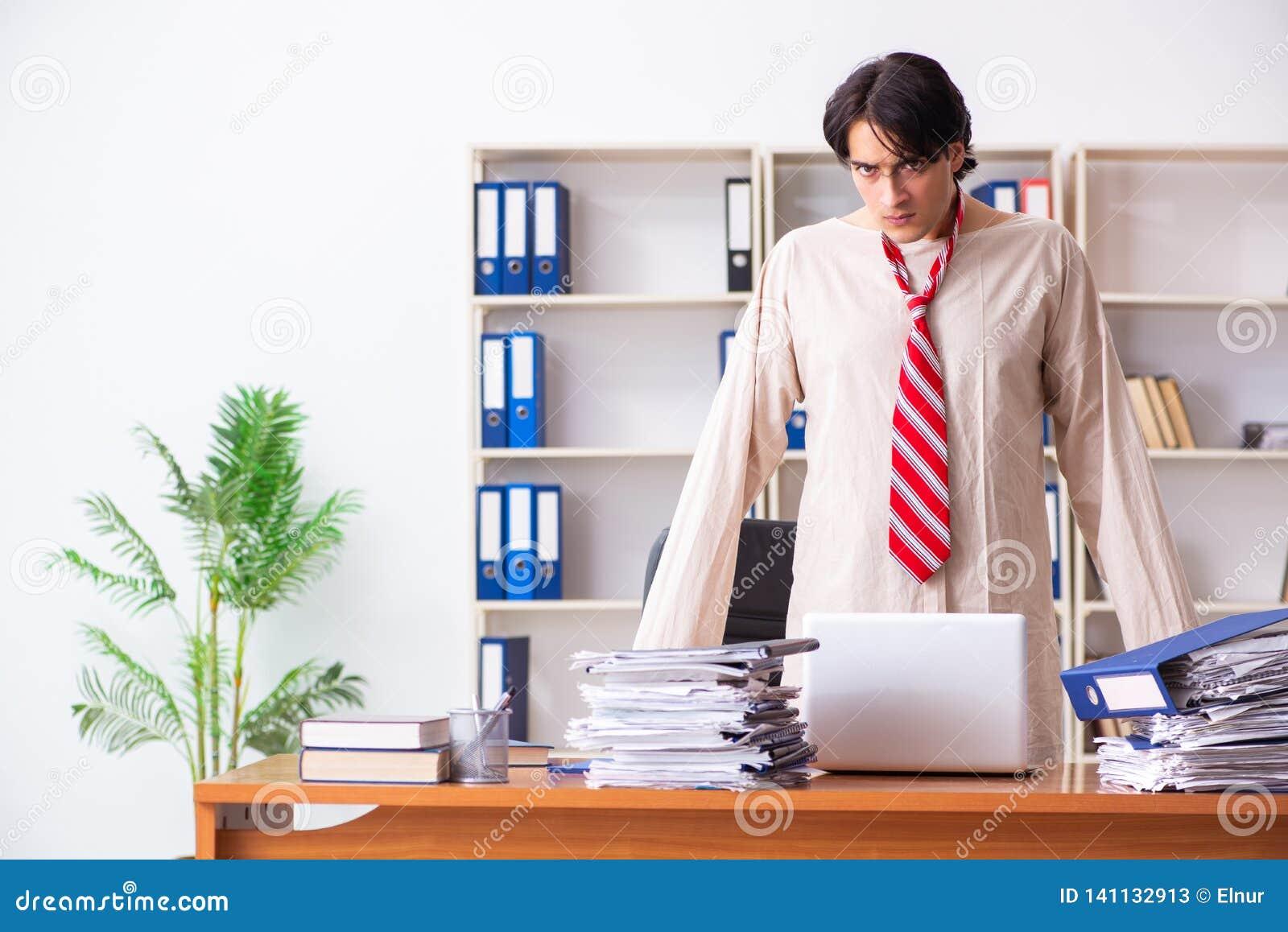 Der verrückte junge Mann in der Zwangsjacke im Büro