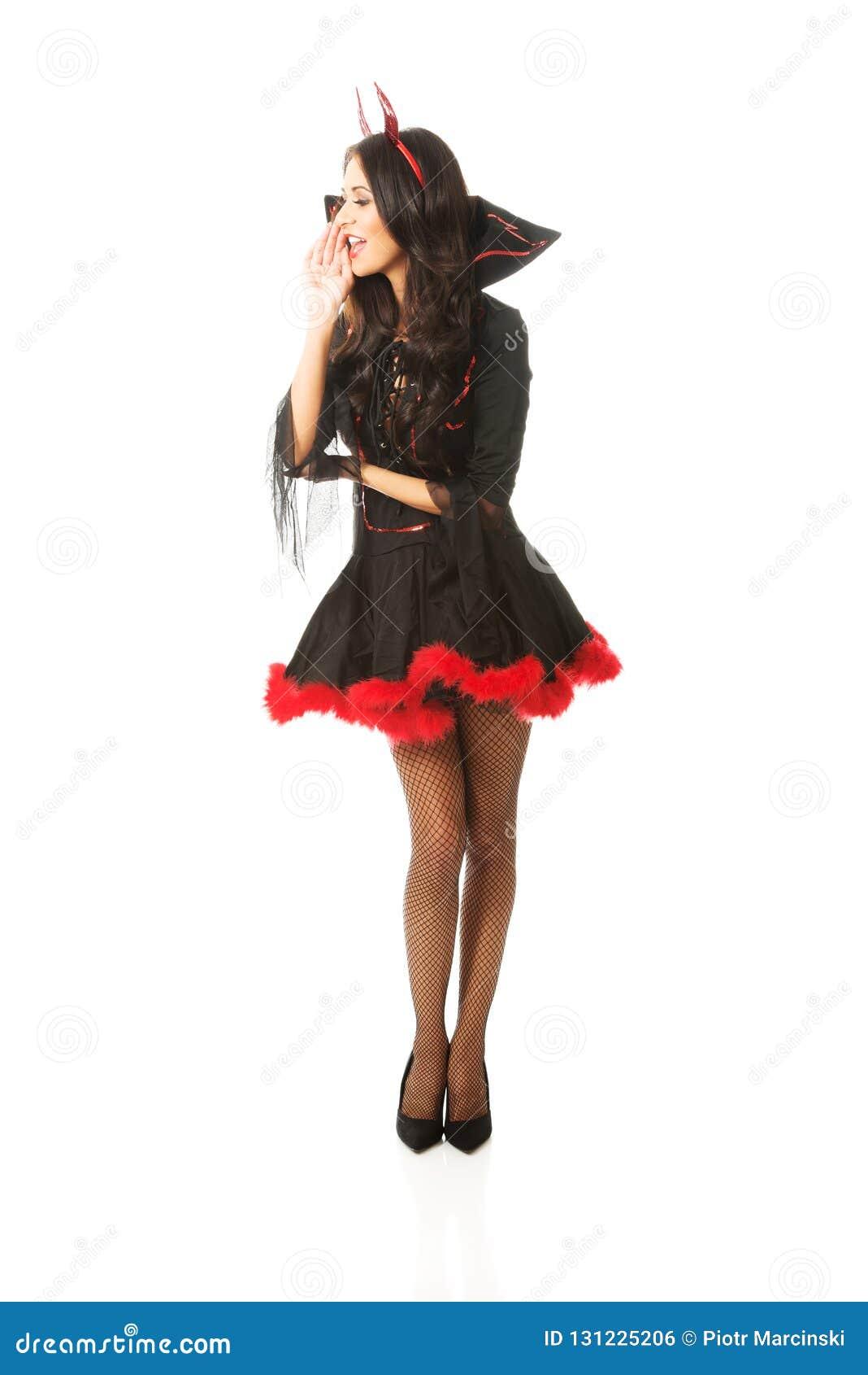 Der in voller Länge tragender Teufel Frau kleidet das Flüstern zu jemand