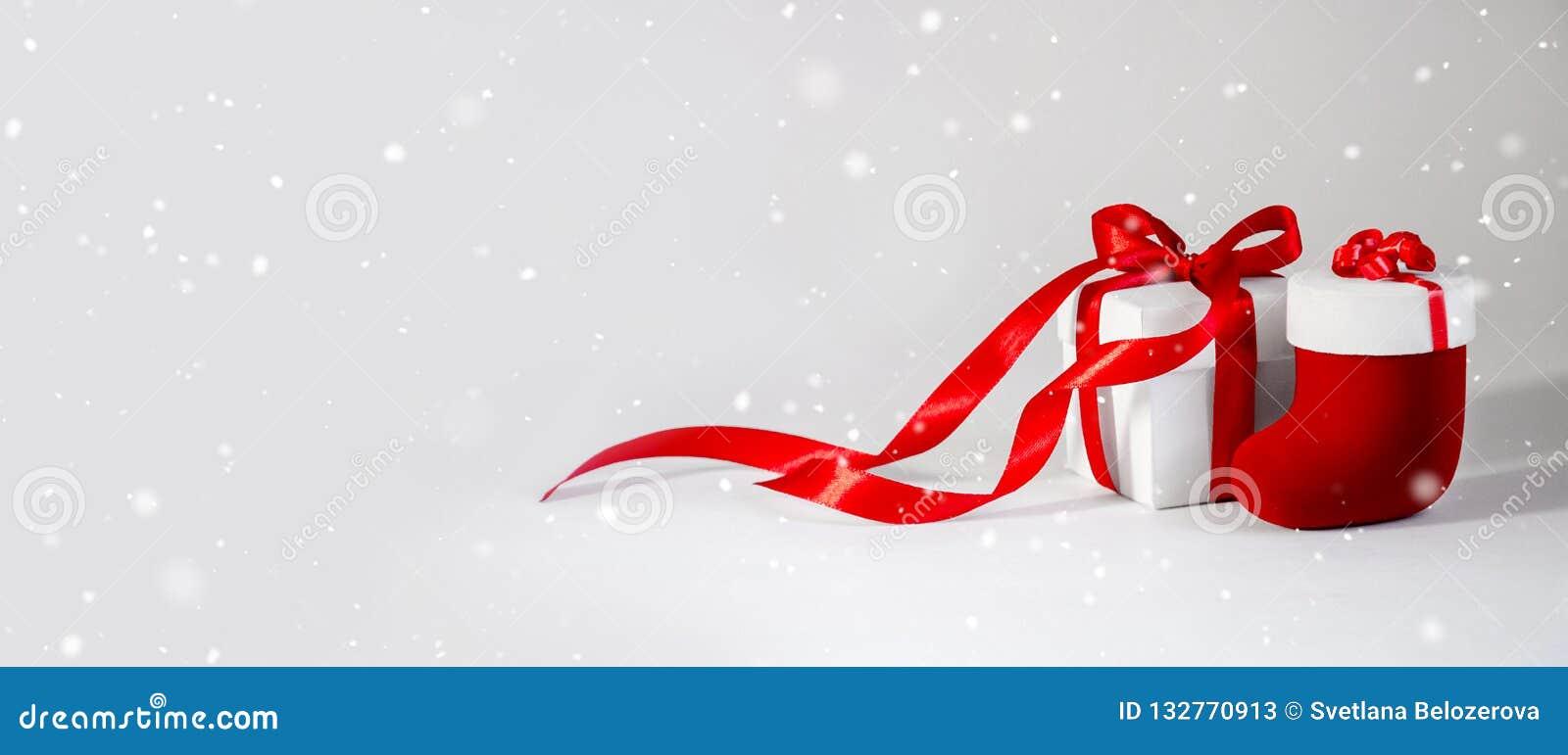 Der weiße Kasten des Weihnachtsgeschenks herein mit rotem Band auf hellem Backgroun