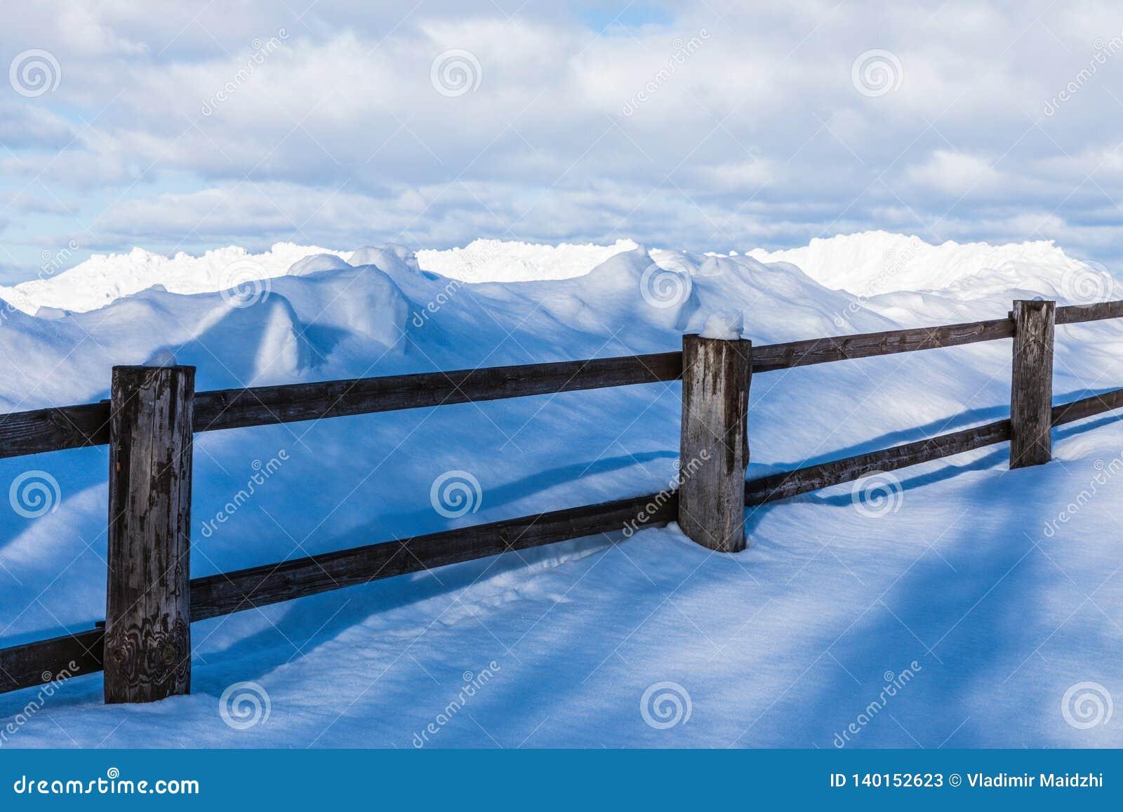Der Zaun oder die Hecke und die Haufen des Schnees in der Landschaft oder im Dorf am kalten Wintertag